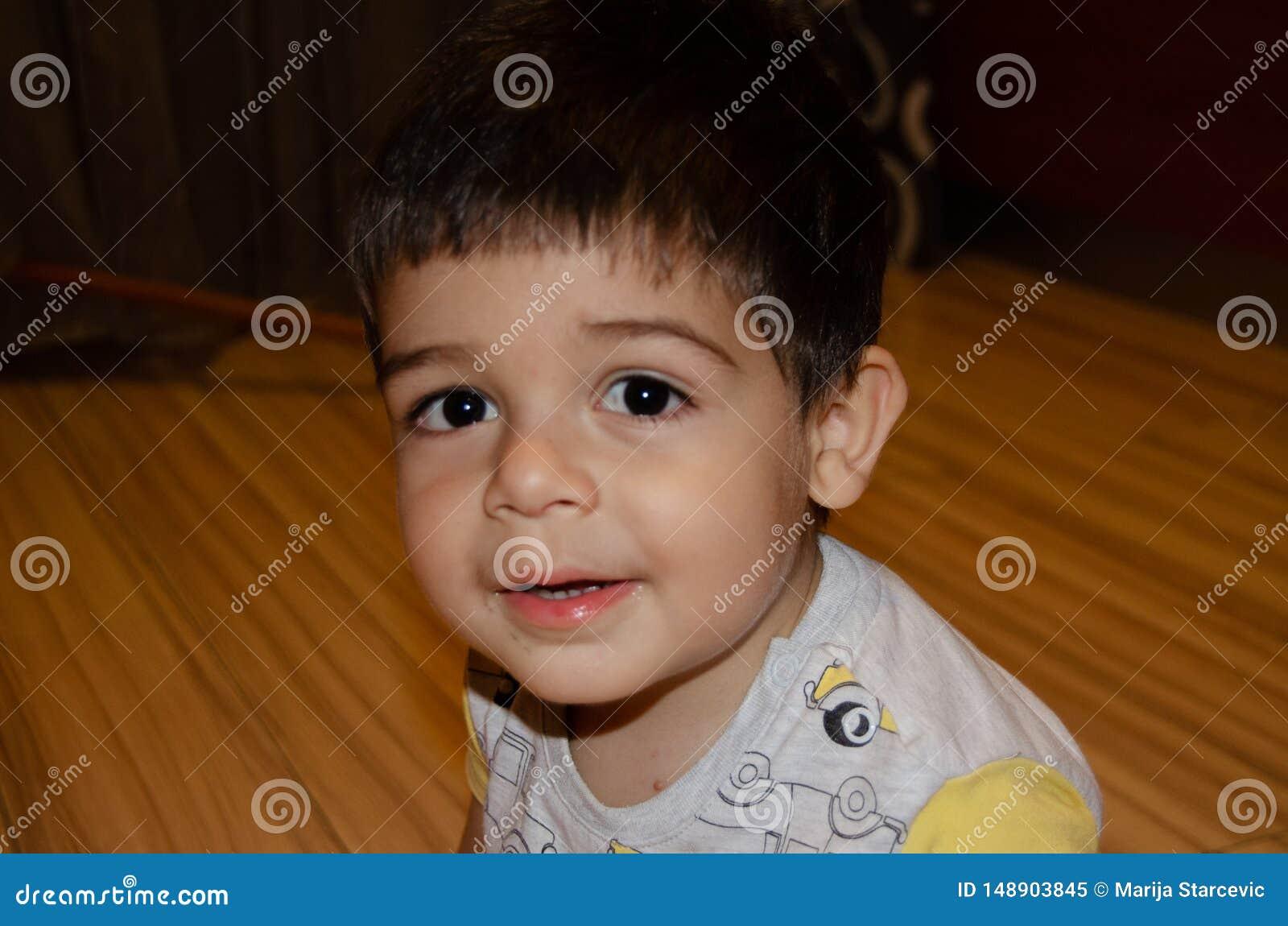 Dois anos bonitos do menino idoso que faz a caras engra?adas o conceito adiantado do desenvolvimento, retrato, express?es da cara