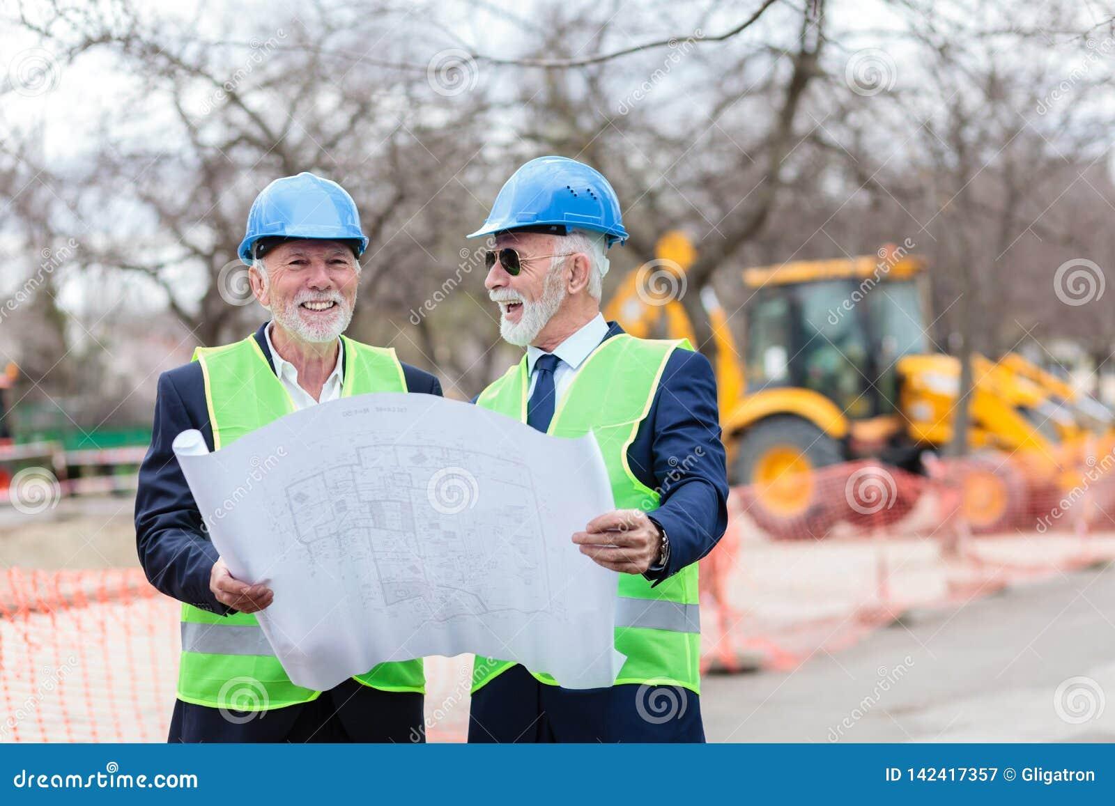 Dois arquitetos ou sócios comerciais superiores que visitam o canteiro de obras, olhando modelos da construção