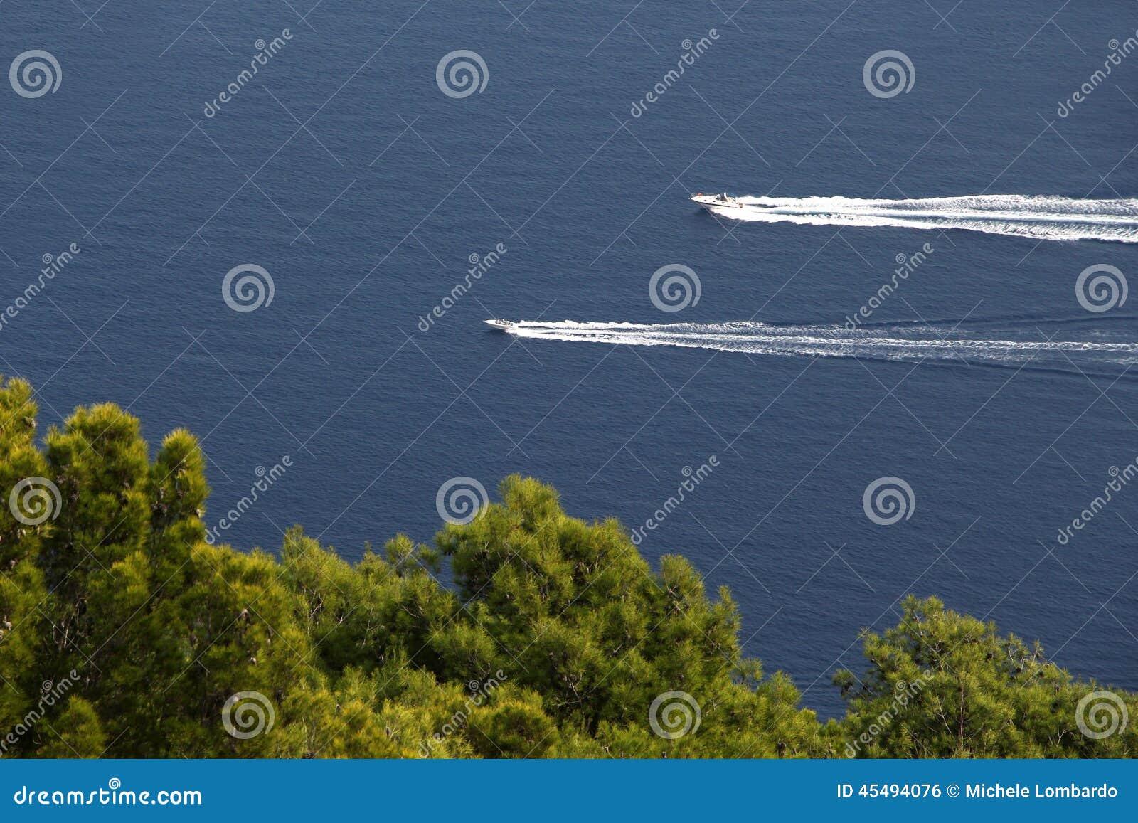 Dois barcos a motor contra um mar azul e árvores