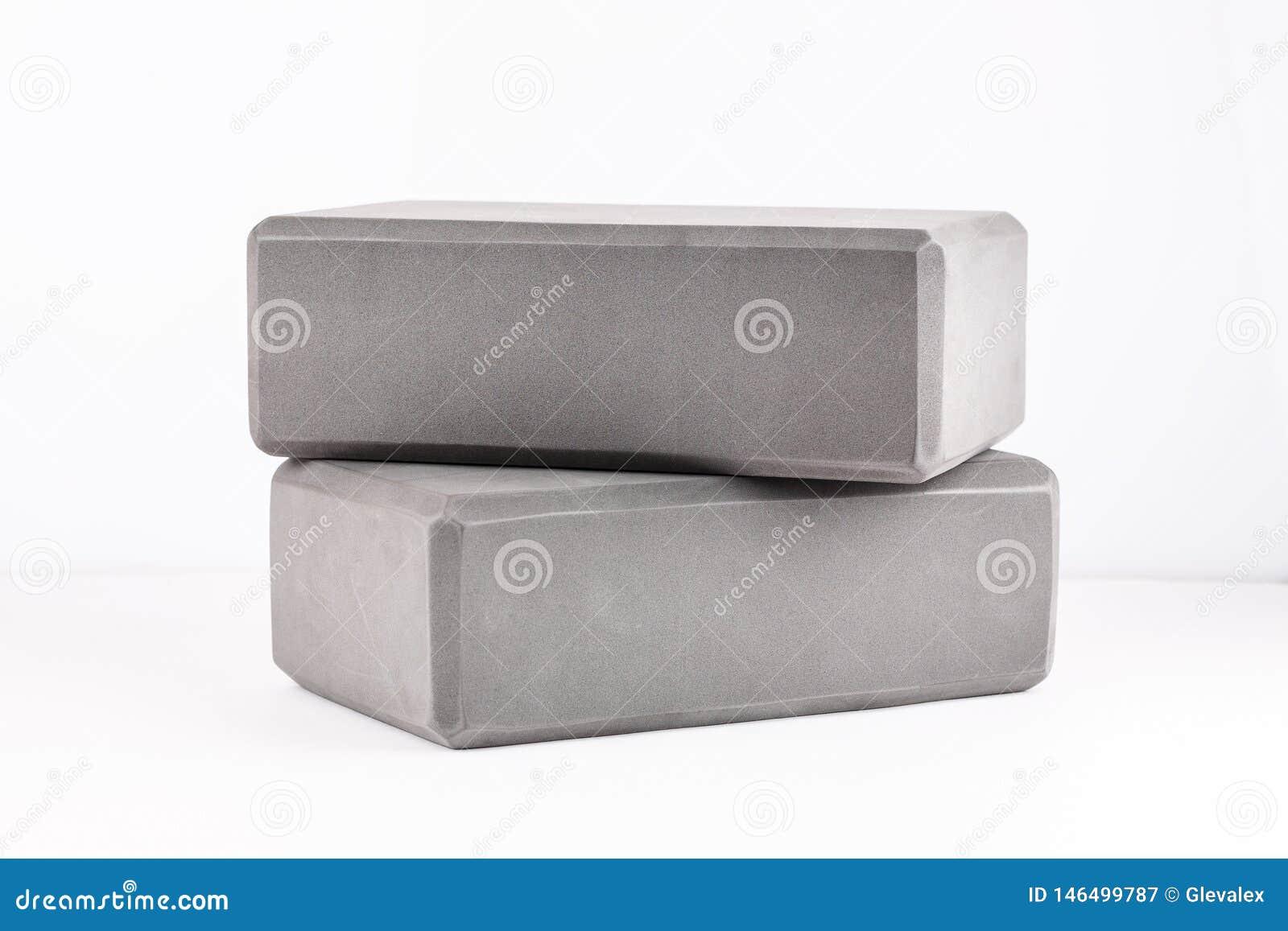Dois blocos cinzentos para a ioga em um branco