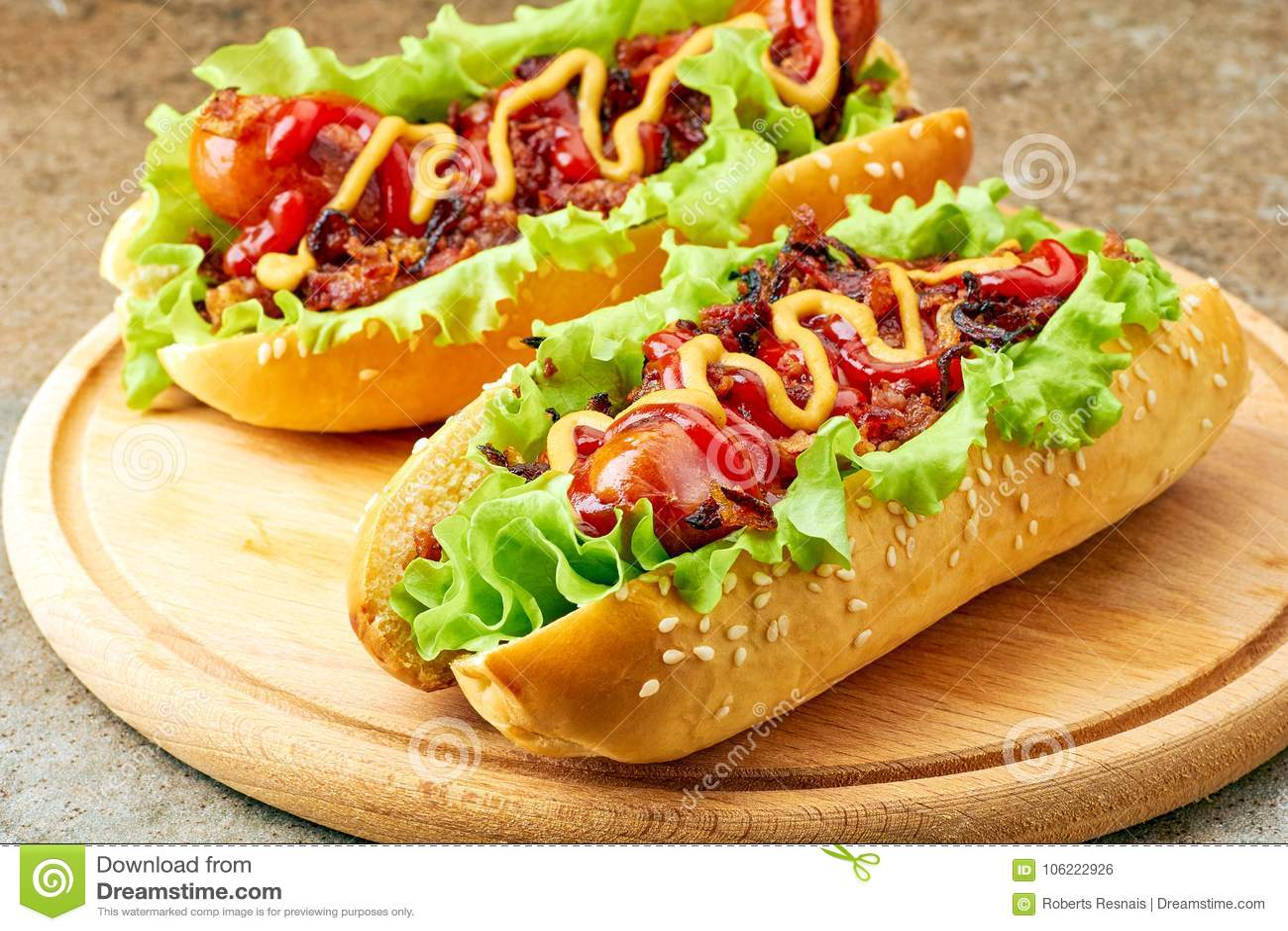Dois cachorros quentes caseiros com coberturas da alface, do bacon e da cebola
