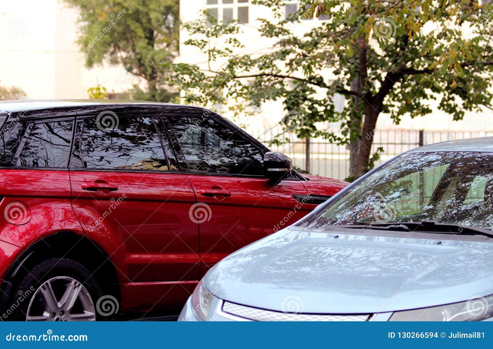 Dois carros vermelhos e cinzentos no parque de estacionamento de uma árvore