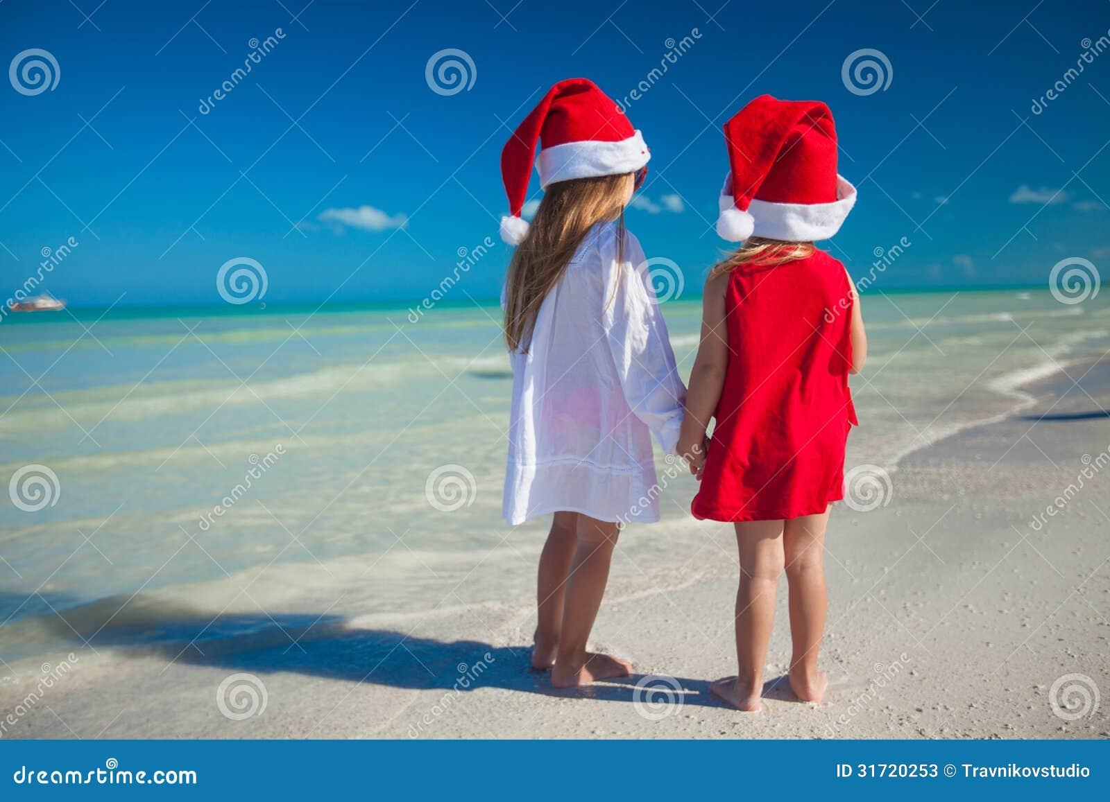 Dois chapéus bonitos pequenos do Natal do girls?in têm o divertimento