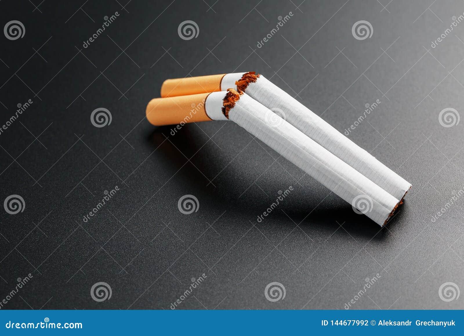 Dois cigarros sob a forma de uma espingarda de cano duplo em um fundo preto com espa?o da c?pia Pare de fumar O conceito de