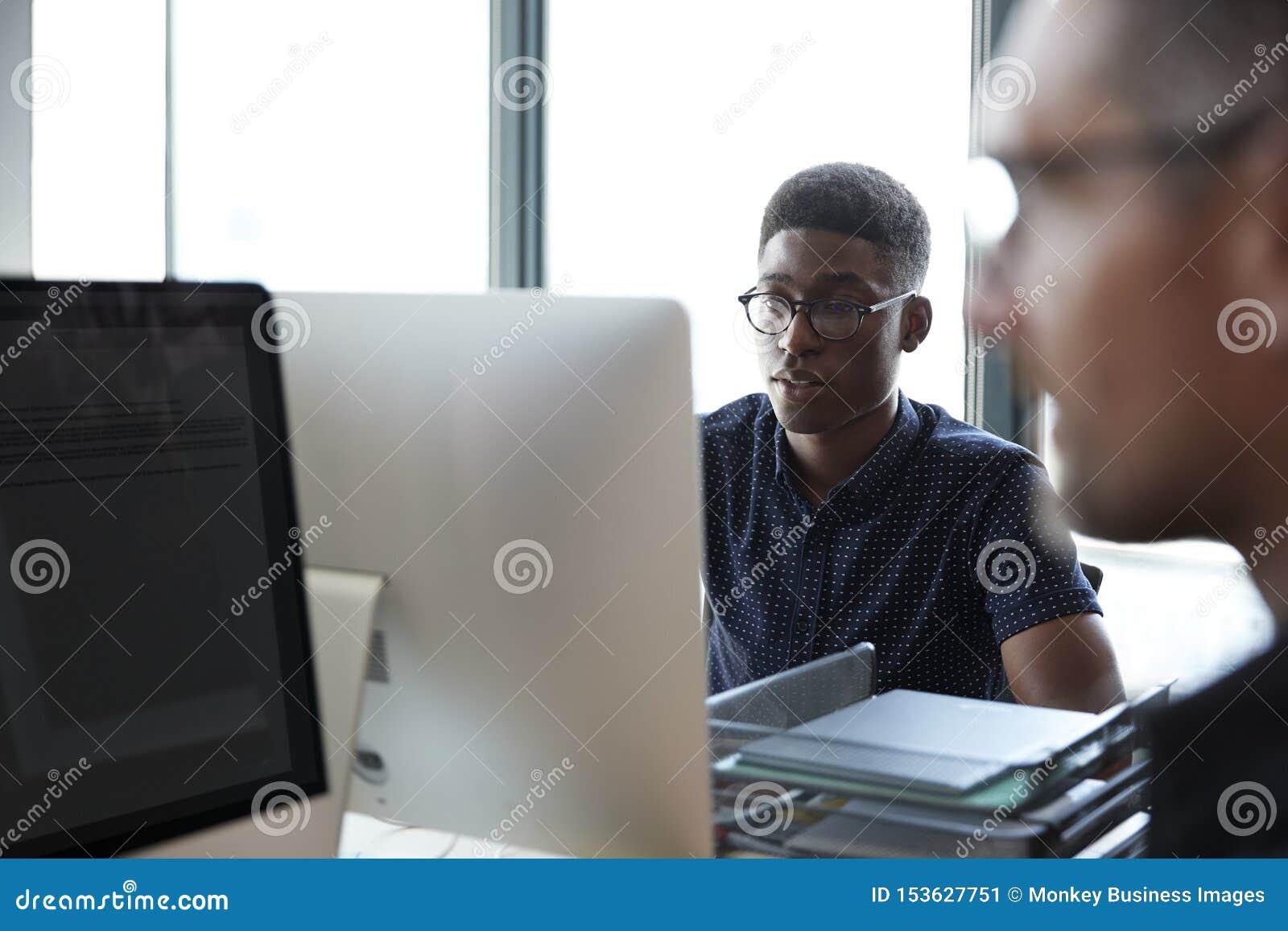 Dois colegas masculinos que trabalham em um escritório criativo, fim acima, foco seletivo