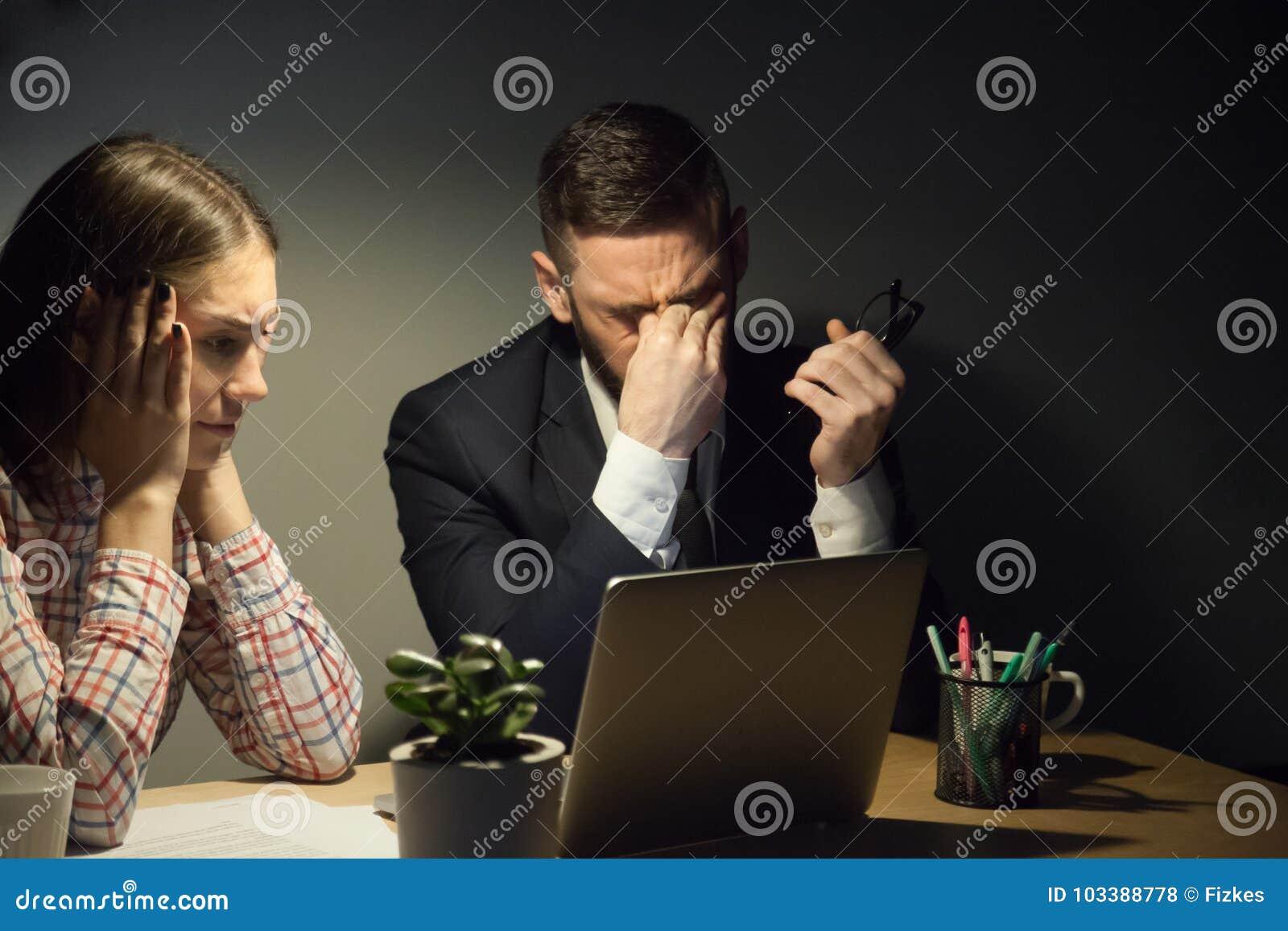 Dois colegas que encontram-se no escritório escuro da noite para resolver um problema