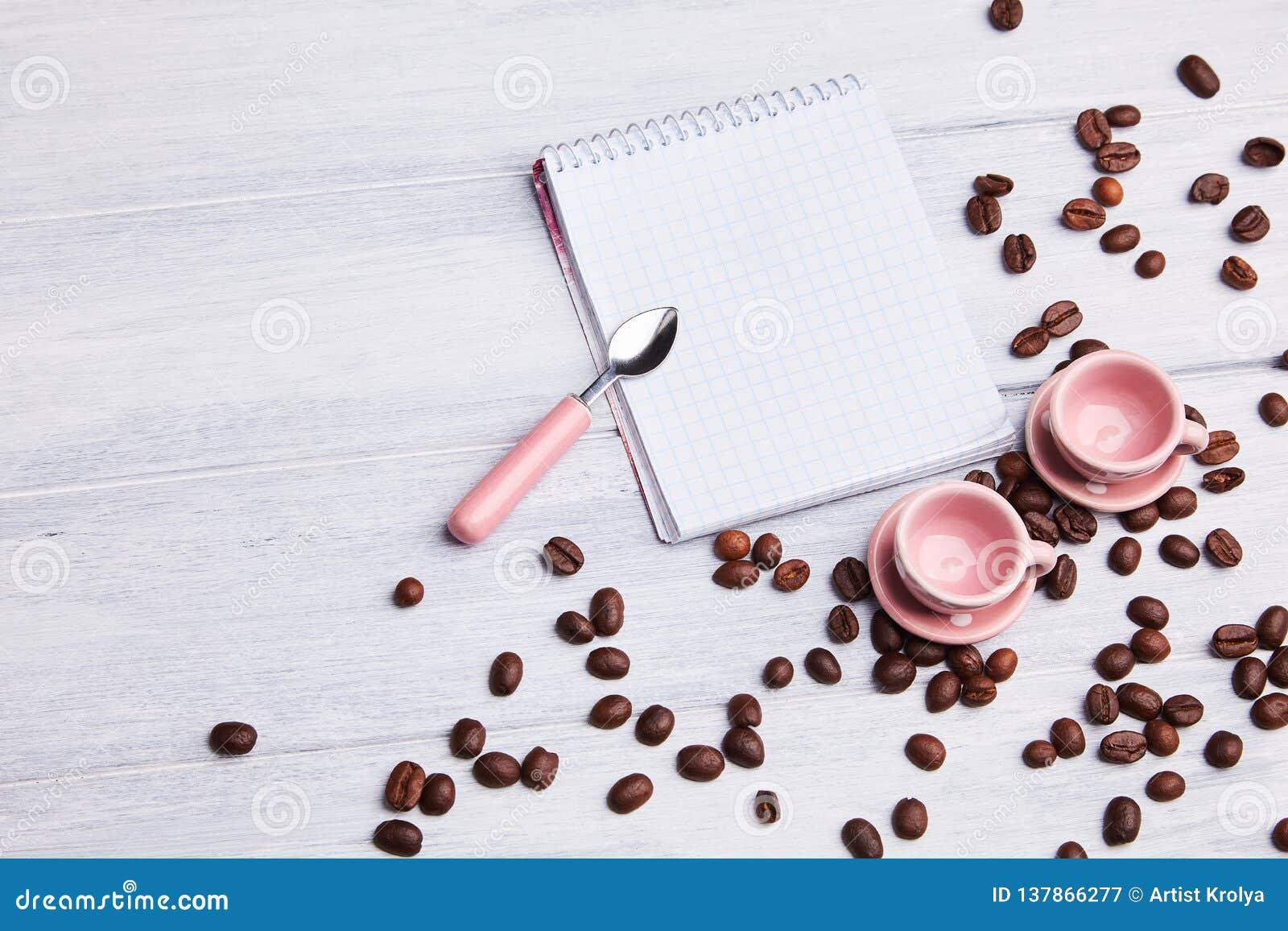 Dois copos cor-de-rosa pequenos na tabela com uma colher, um bloco de notas e uns feijões de café dispersados em um fundo de made