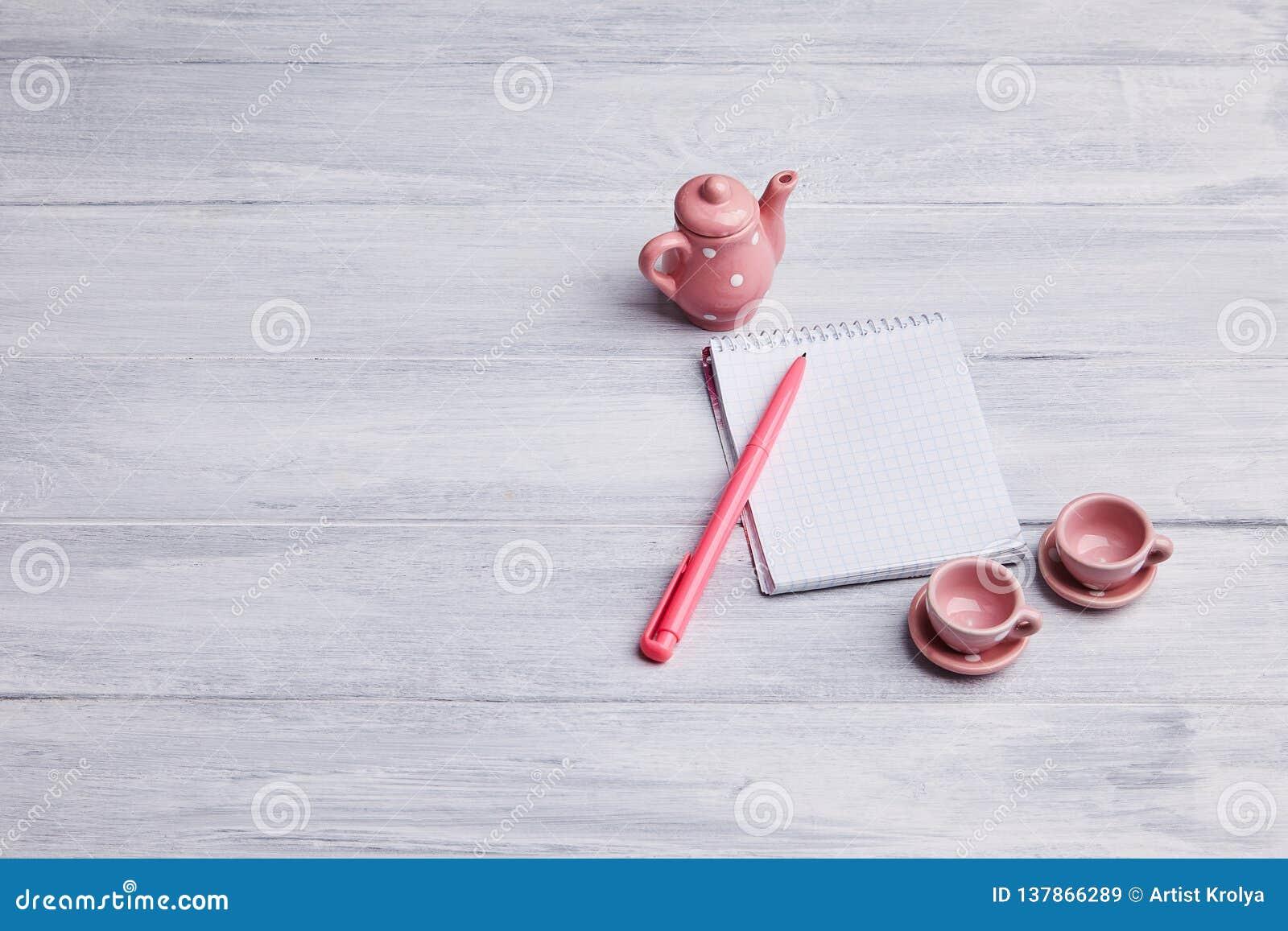 Dois copos de chá cor-de-rosa pequenos com chaleira em um fundo de madeira Cartão com um caderno e uma pena