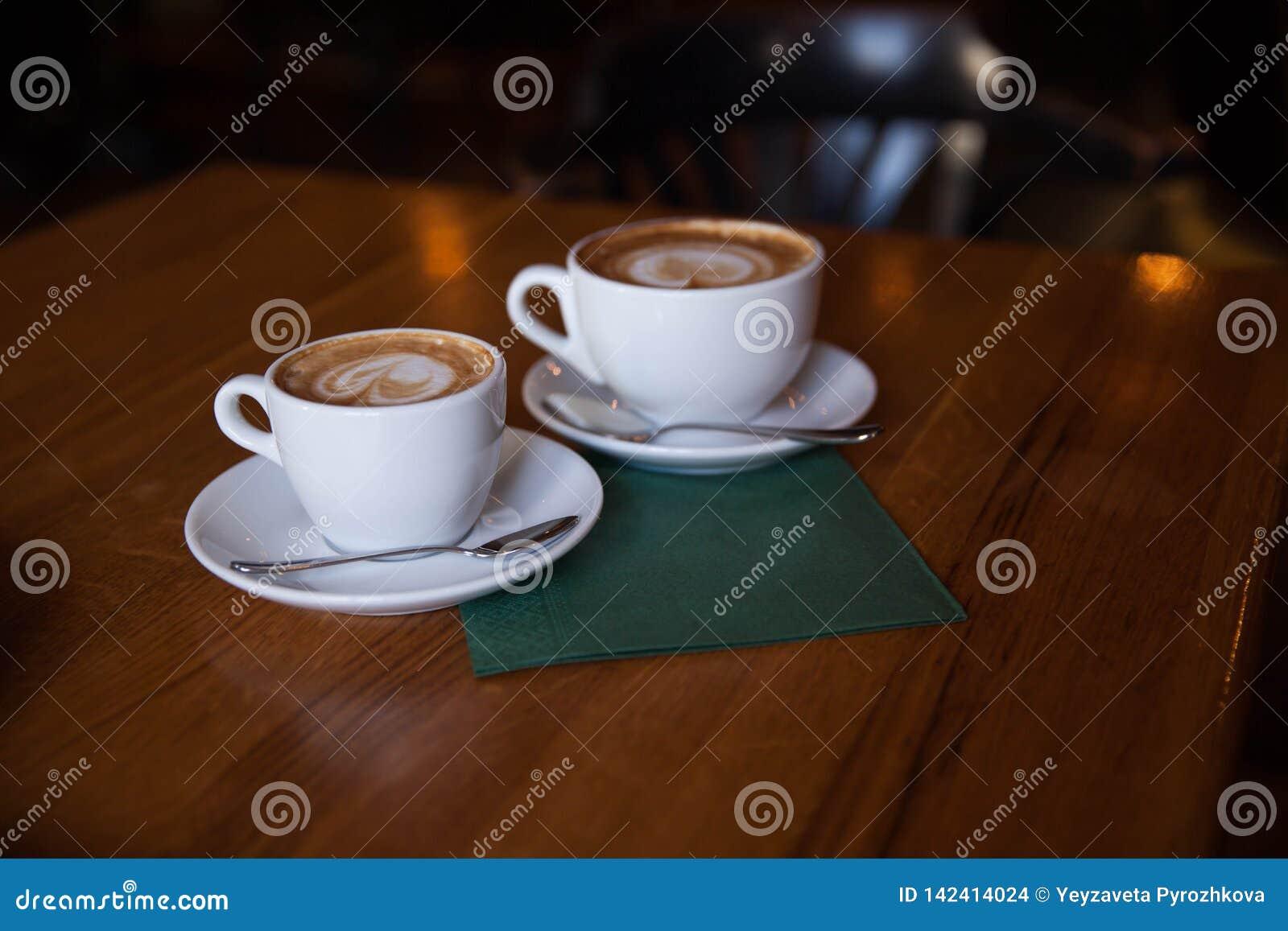 Dois copos do cappuccino em uma tabela de madeira