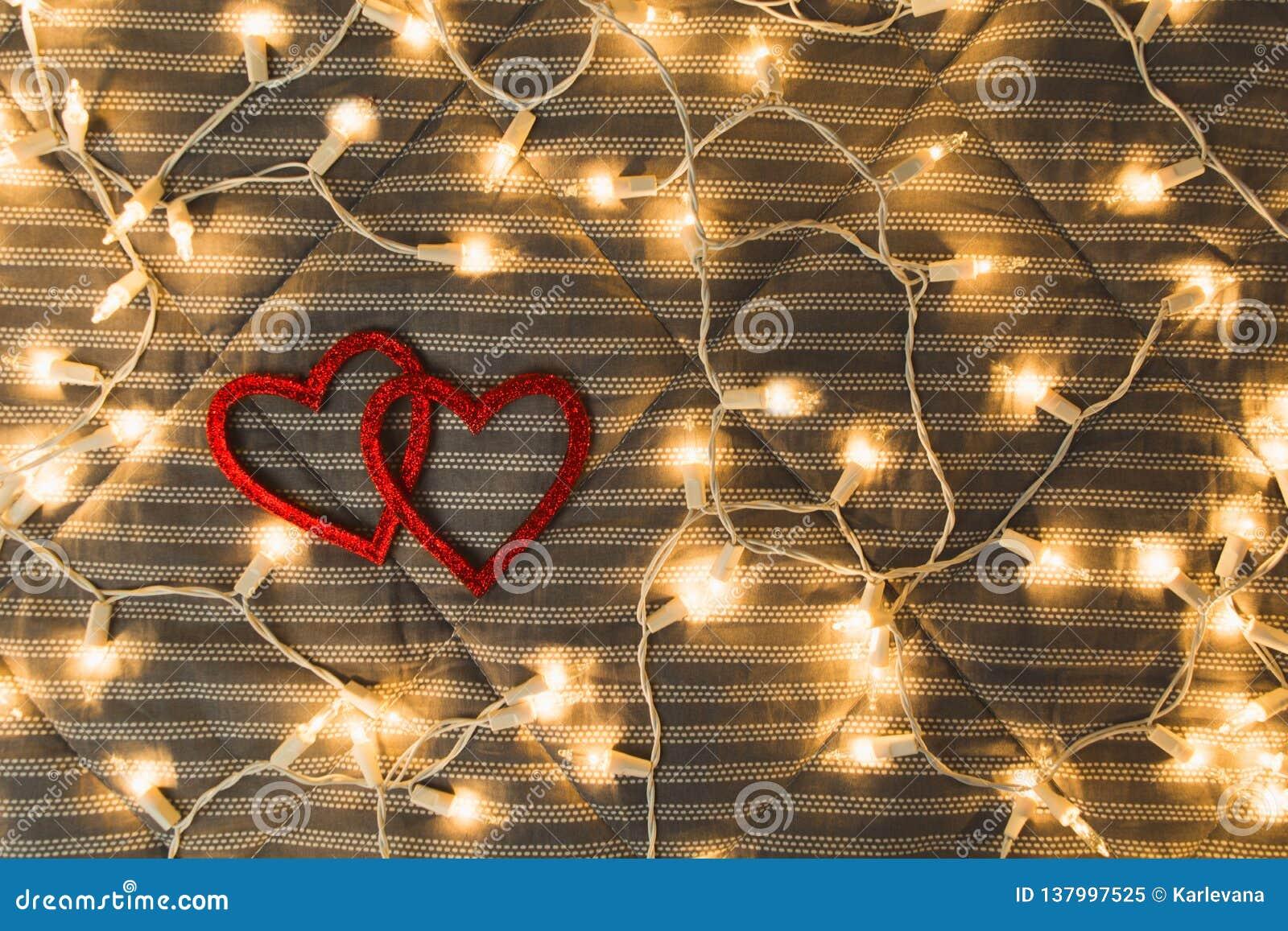 Dois corações com luzes amarelas, conceito acolhedor dos pares, o dia de Valentim