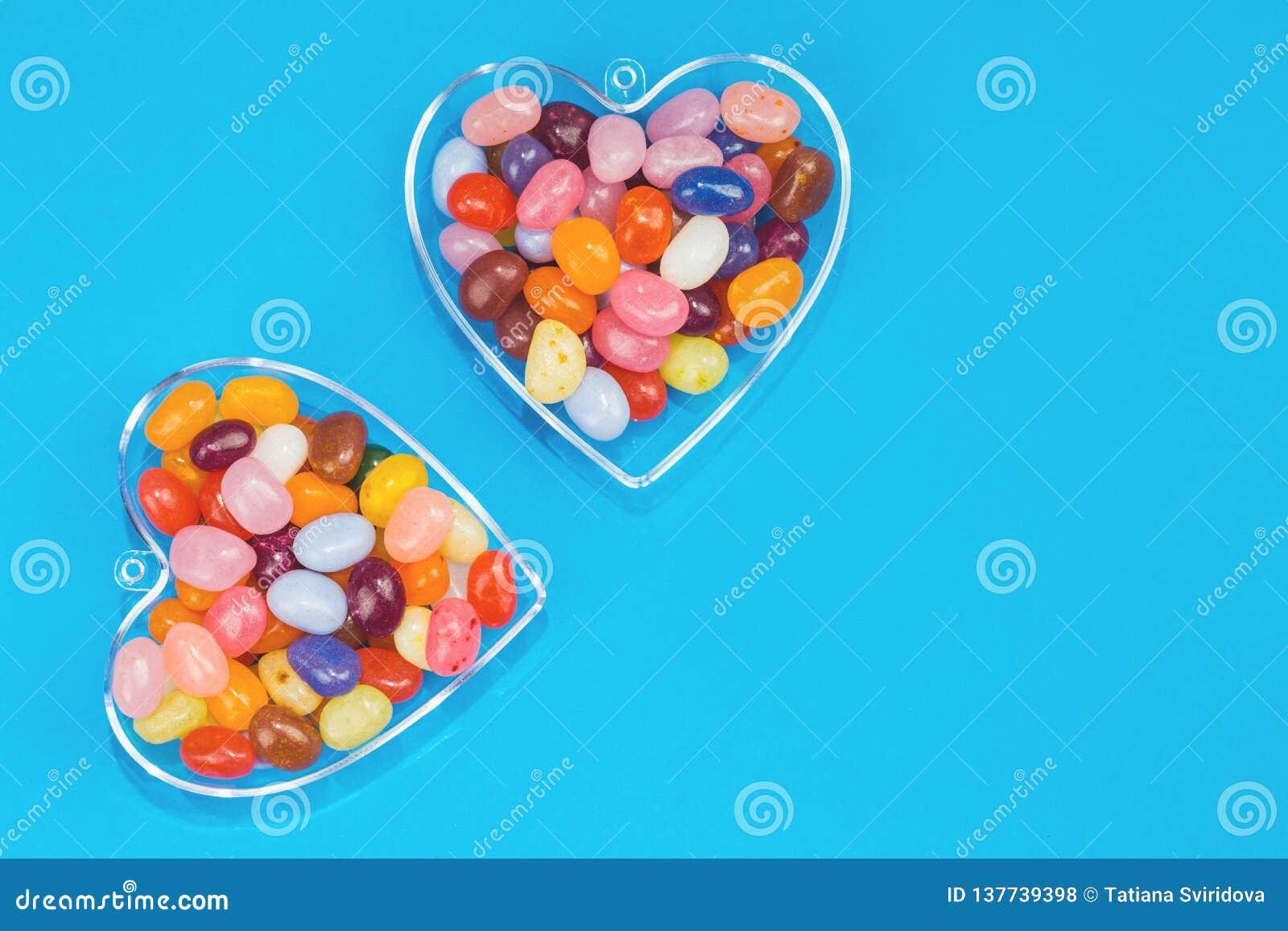 Dois corações com os doces no fundo azul