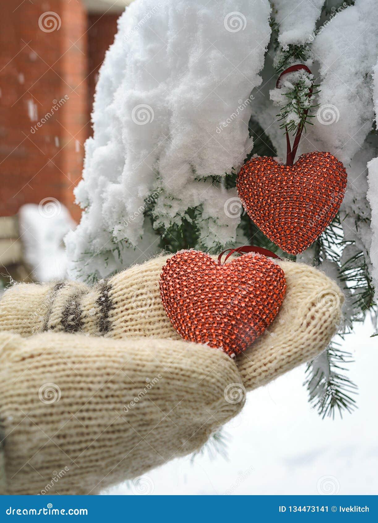 Dois corações e mãos vermelhos de matéria têxtil no fundo nevado pesado do ramo do abeto, perto da casa do tijolo vermelho Feliz