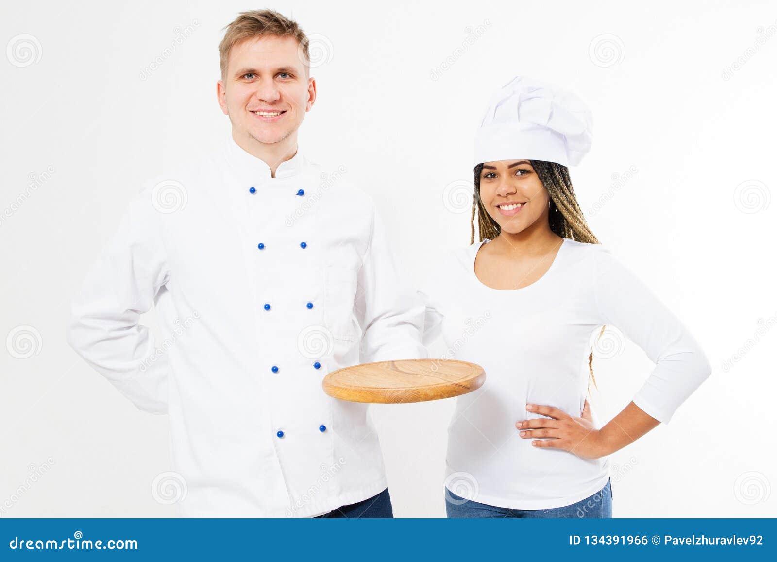 Dois cozinheiros chefe de sorriso mantêm a mesa vazia da pizza isolada no fundo branco