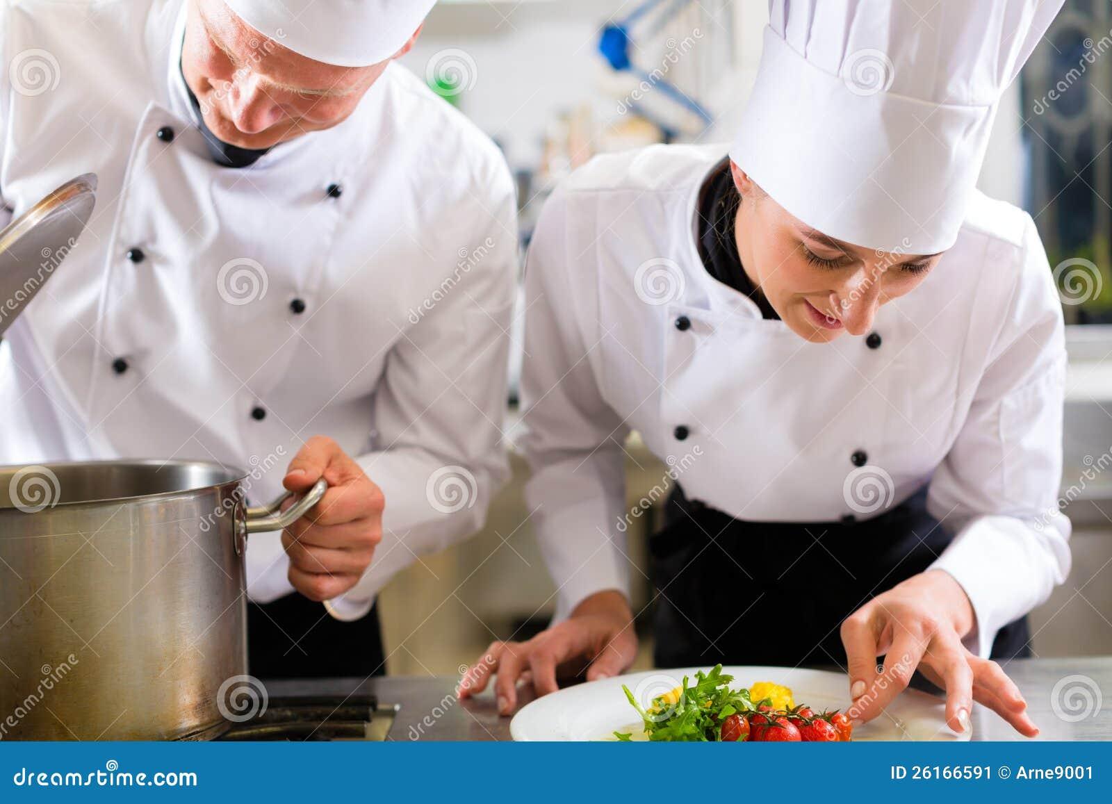 Dois cozinheiros chefe na equipe na cozinha do hotel ou do restaurante