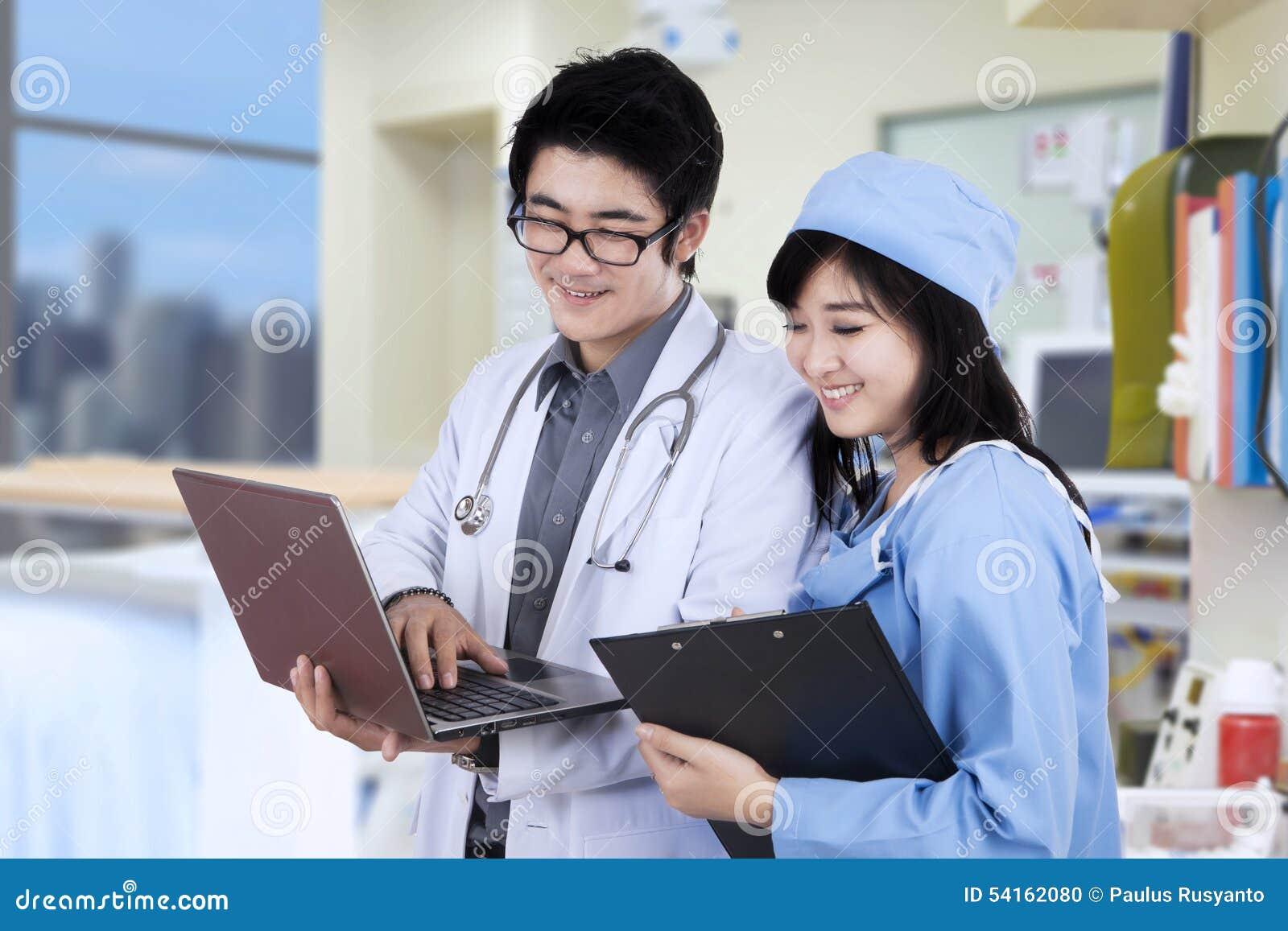 Dois doutores que usam-se com o portátil no hospital