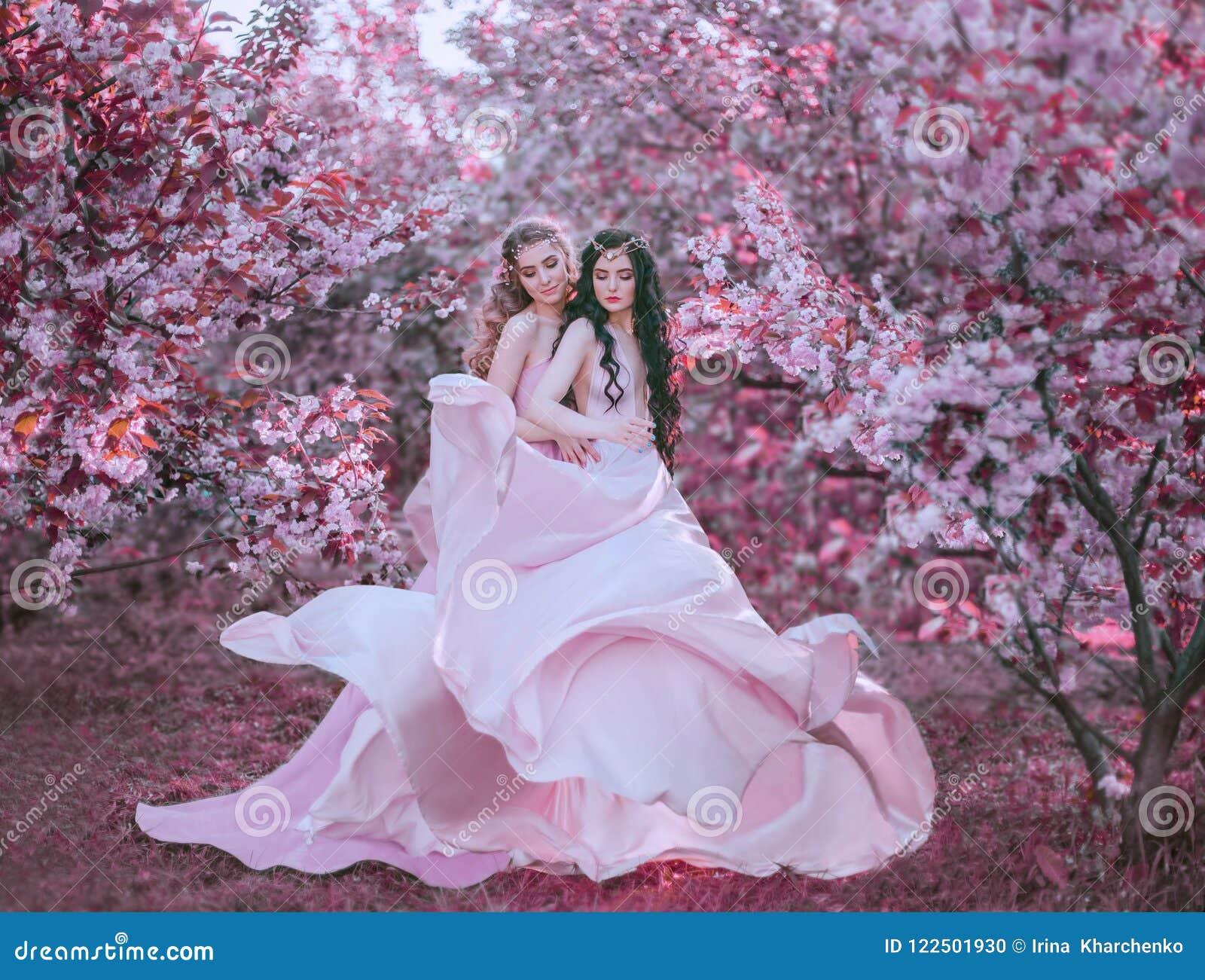 Dois duendes surpreendentes andam no jardim fabuloso da flor de cerejeira Princesas em luxuoso, longo, vestidos do rosa que vibra