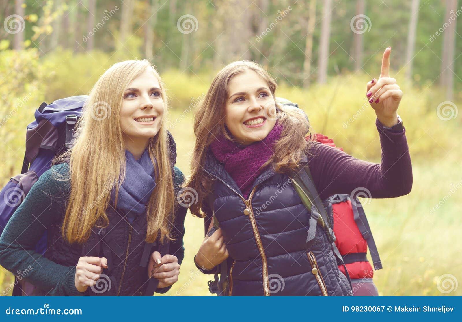 Dois felizes e meninas bonitas que andam na floresta e nos pântanos acampamento