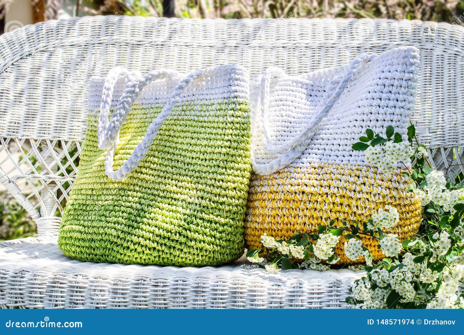 Dois fizeram malha sacos feitos à mão em estadas amarelas, verdes e brancas das cores no sofá de vime branco no jardim com spirea
