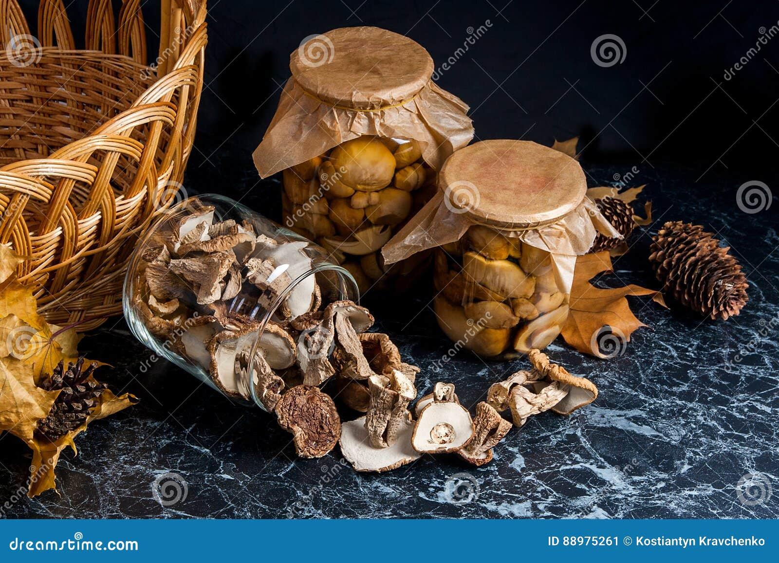 Dois frascos de vidro com os cogumelos selvagens no fundo de mármore preto