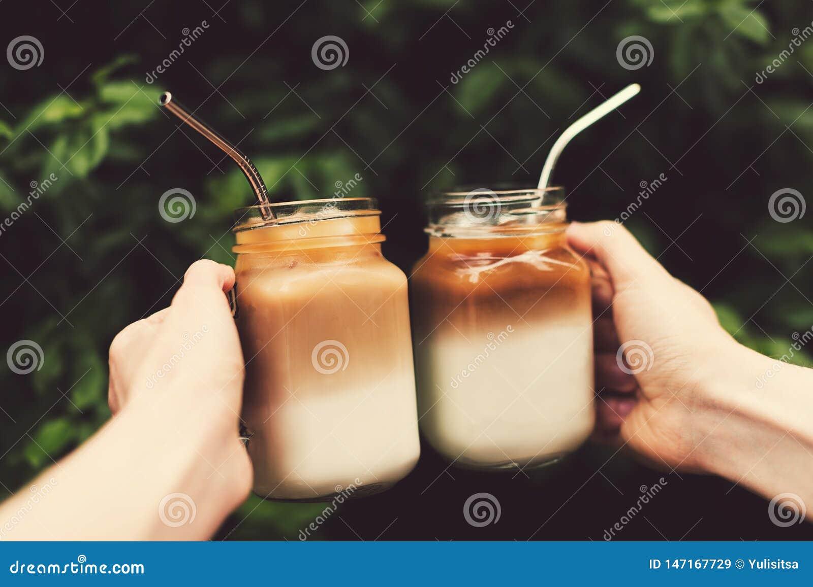 Dois frascos de vidro do café de gelo nas mãos da mulher e do homem