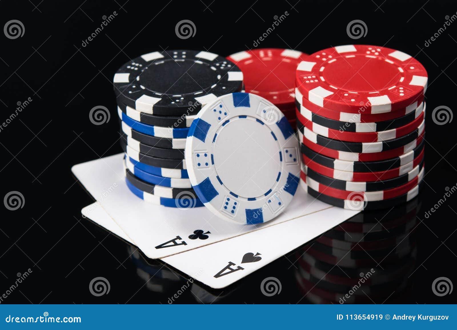 Dois grandes cartões de jogo com microplaquetas de pôquer em um fundo escuro