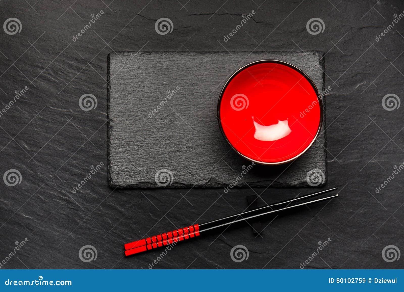Dois hashis e placa vermelha no fundo de pedra preto com copyspace