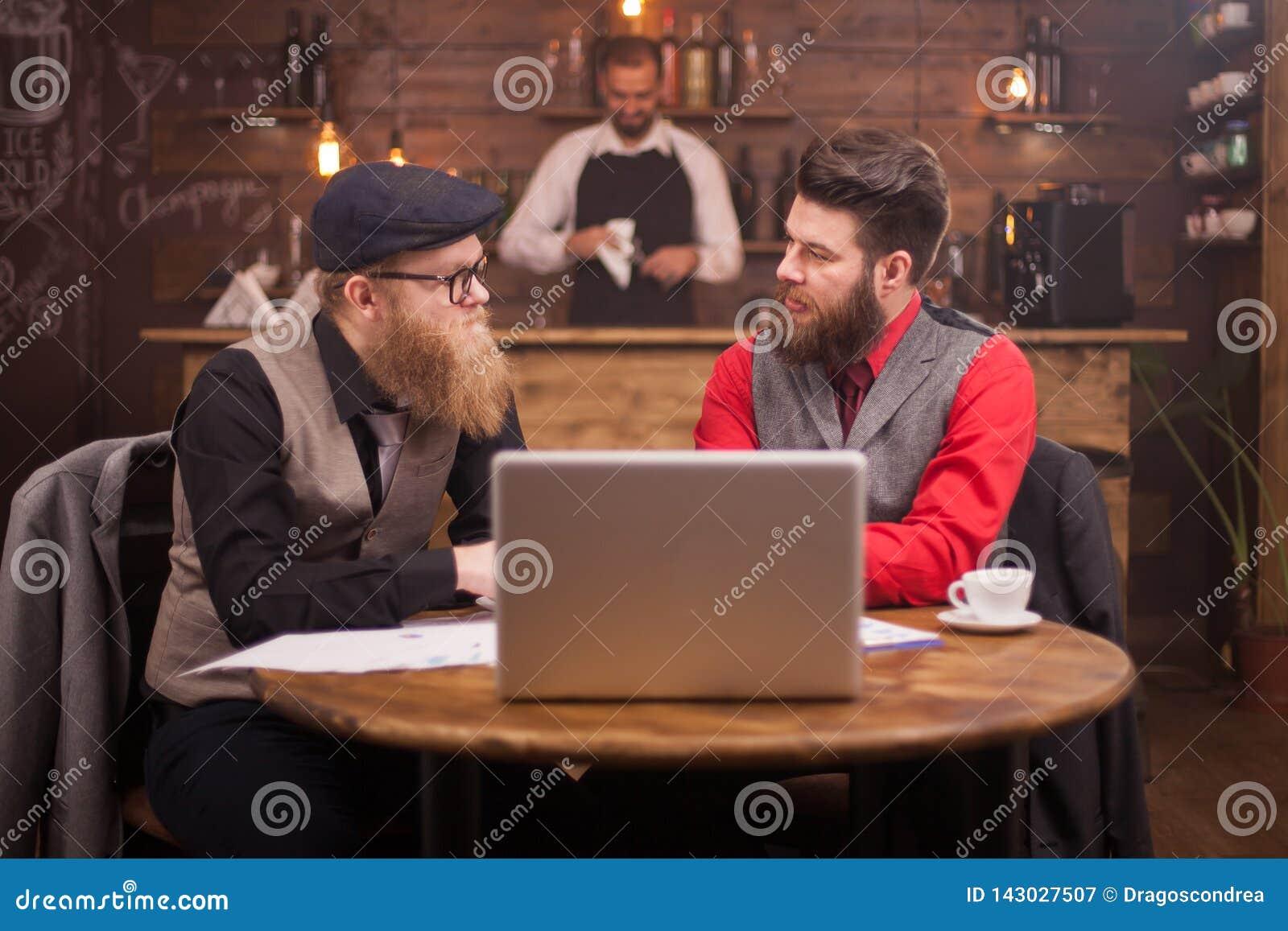 Dois homens de negócios consideráveis que olham se ao falar sobre finanças em um bar do vintage