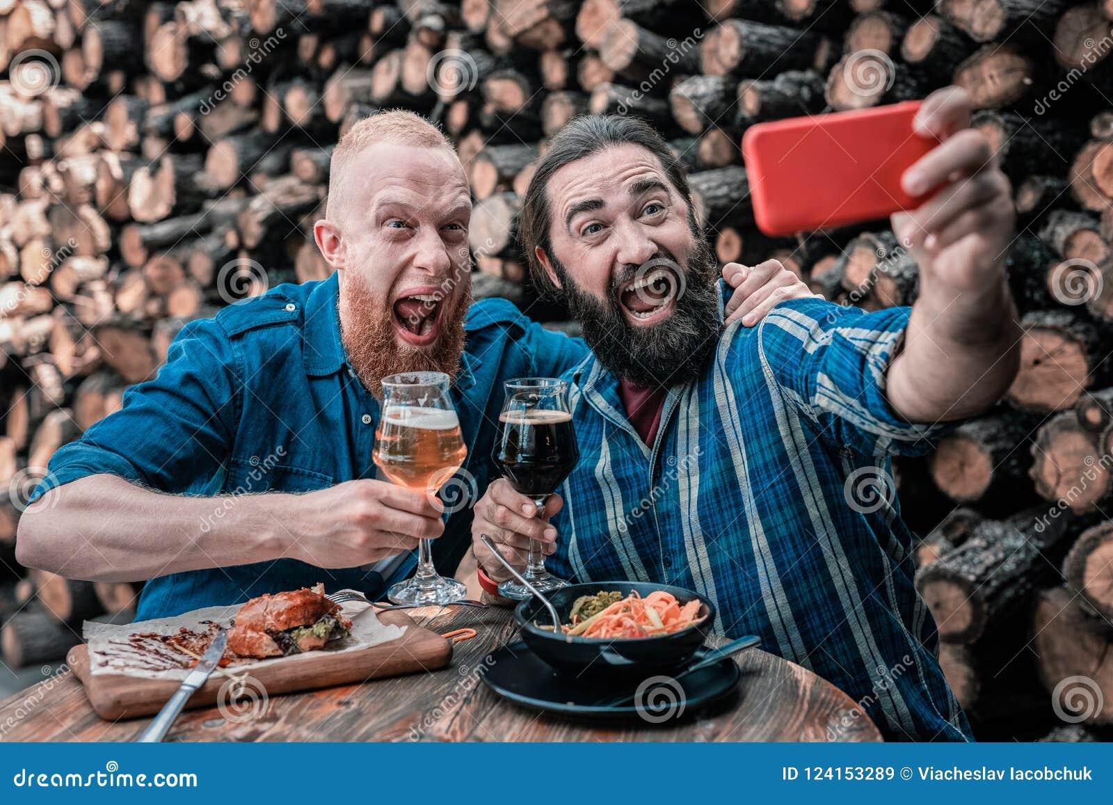 Dois homens de negócios maduros que fazem a foto que senta-se junto no bar