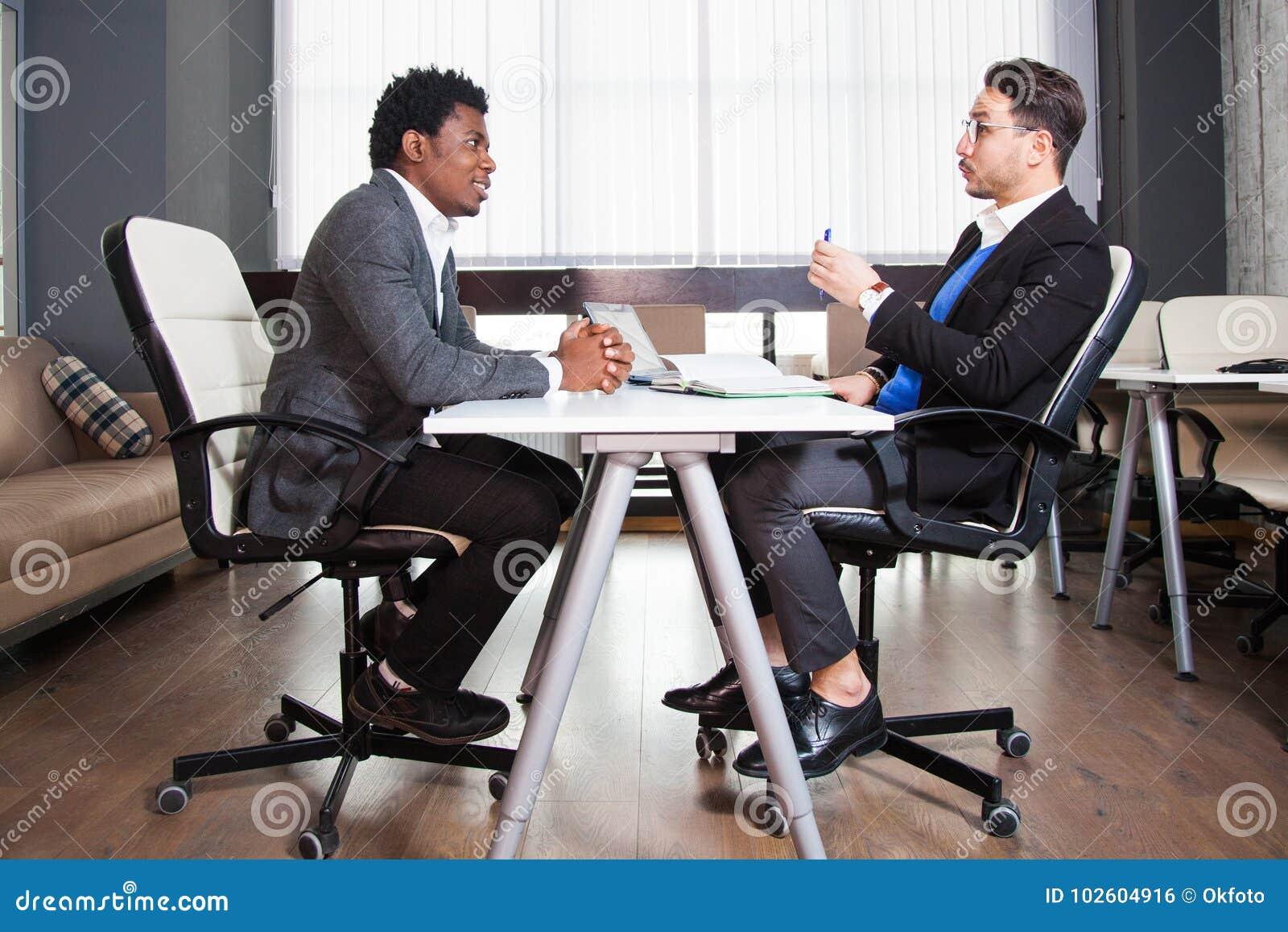 Dois homens de negócios novos, mesa branca, entrevista de trabalho, trabalhos de equipa