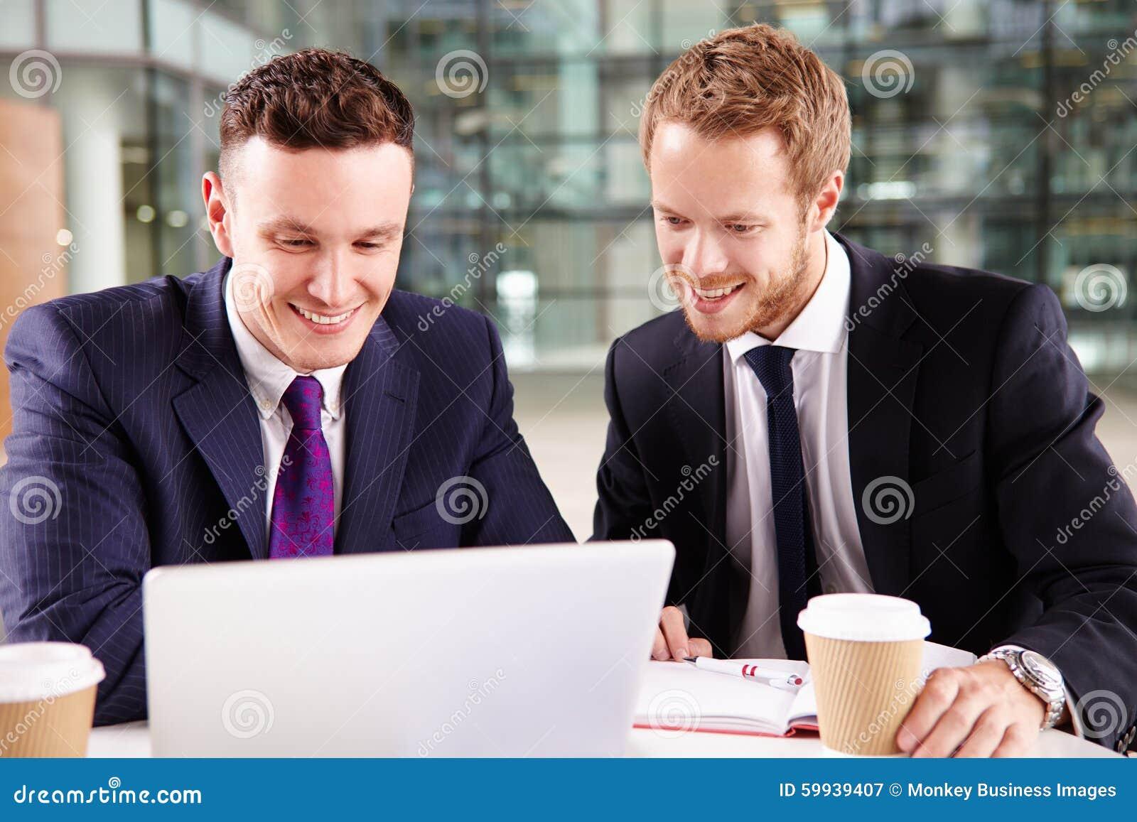 Dois homens de negócios novos que comem o café, usando um laptop