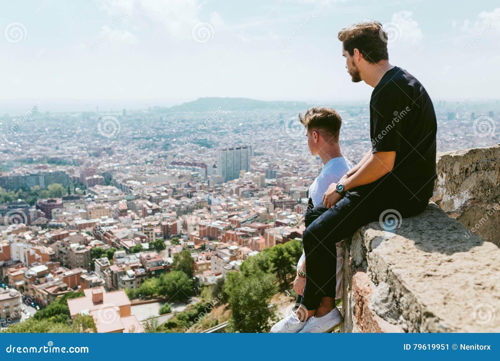 Dois homens novos que olham as vistas formam a parte superior de uma montanha