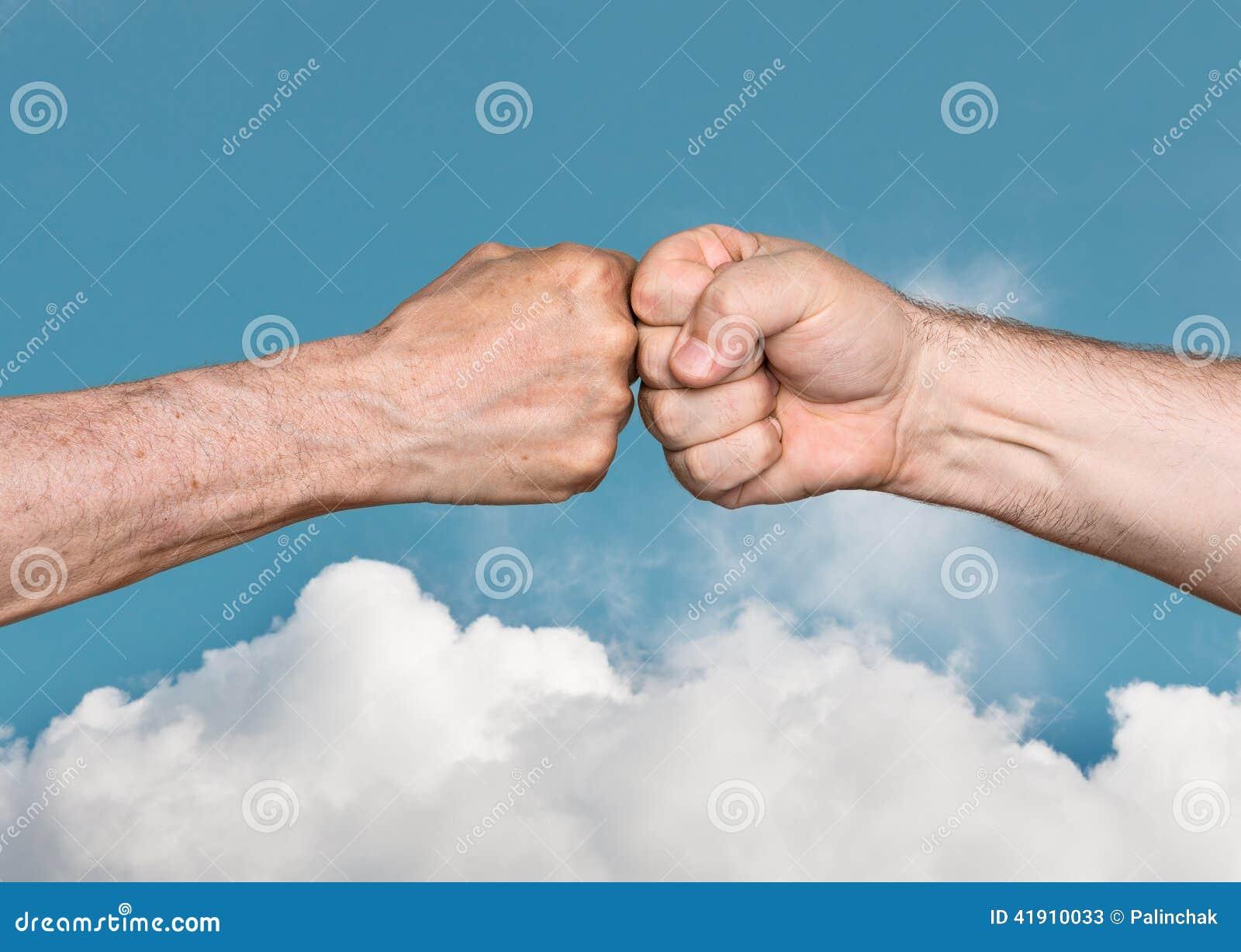 Dois homens que colidem os punhos