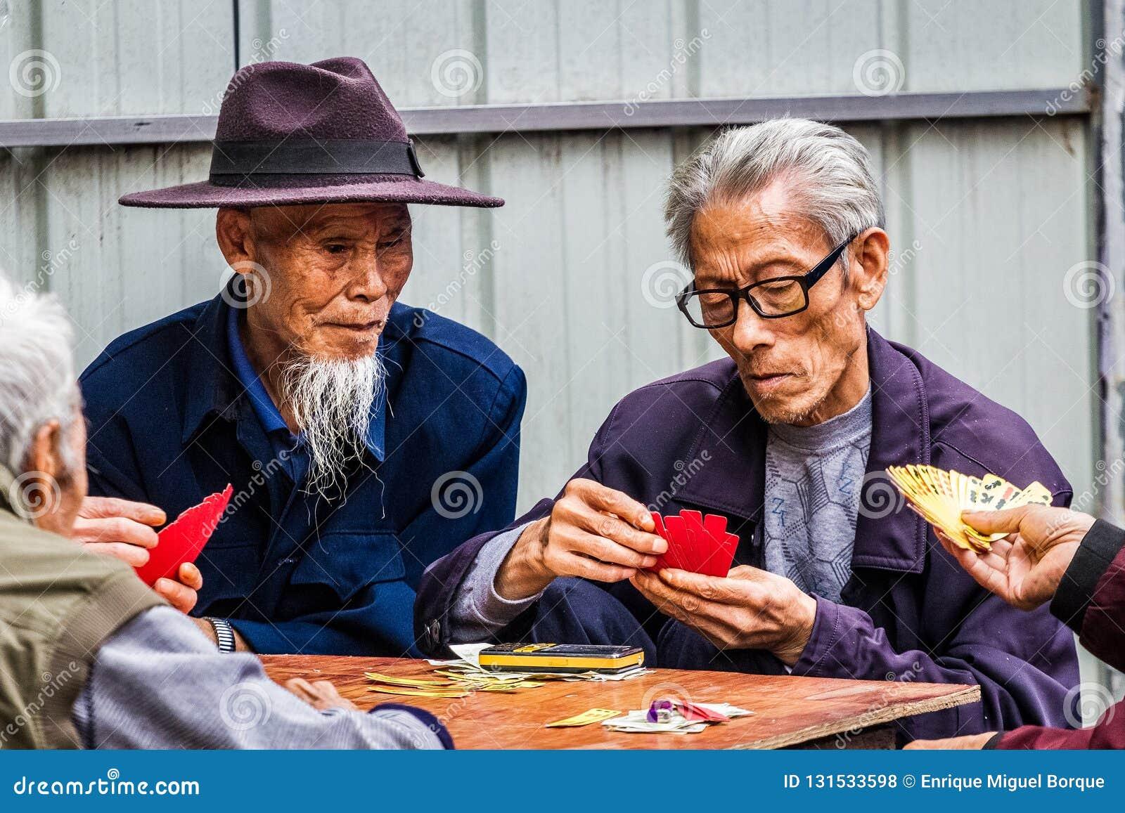 Dois homens que jogam cartões chineses tradicionais