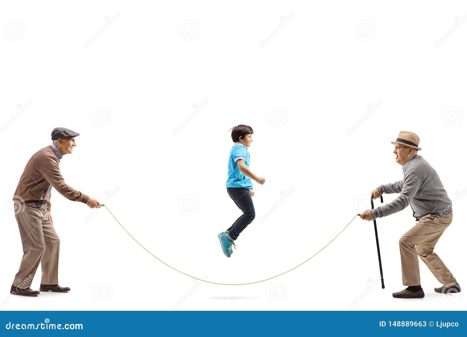Dois homens superiores que guardam uma corda e um salto do menino