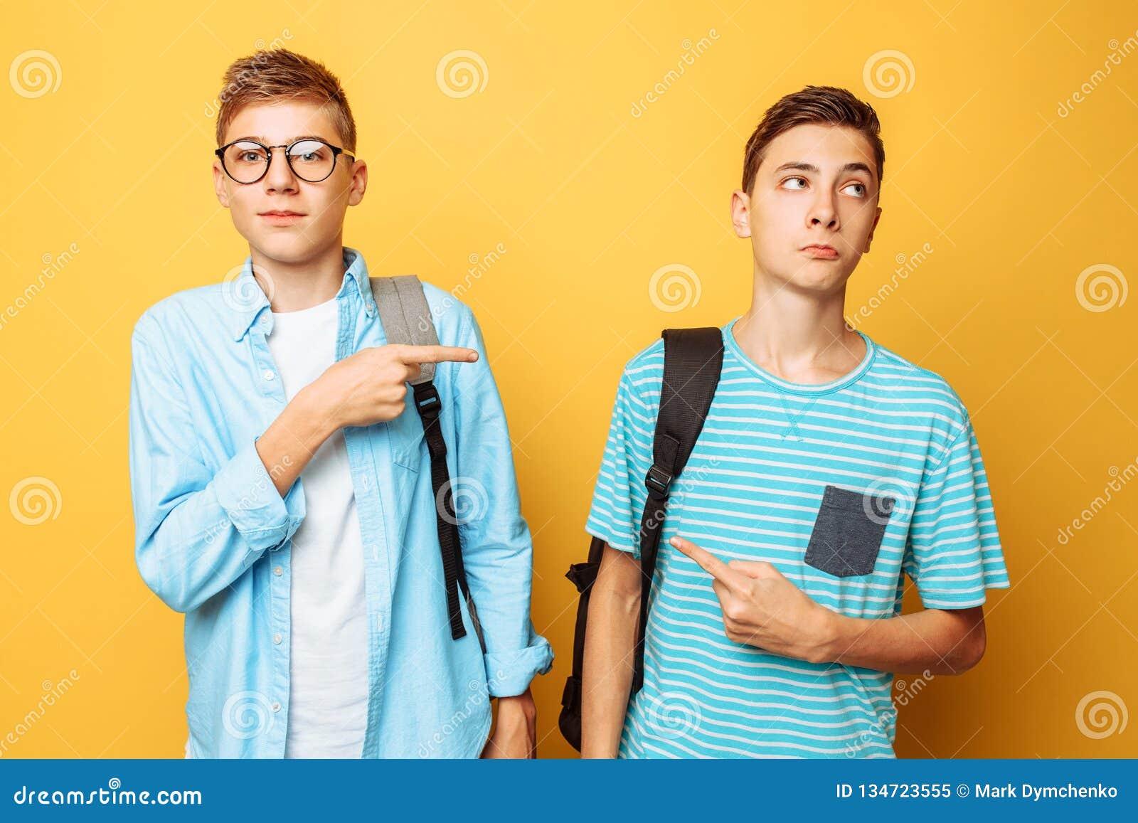 Dois indivíduos adolescentes apontam em se com seus polegares, culpa e não querem admitir sua culpa, isolada em um fundo amarelo