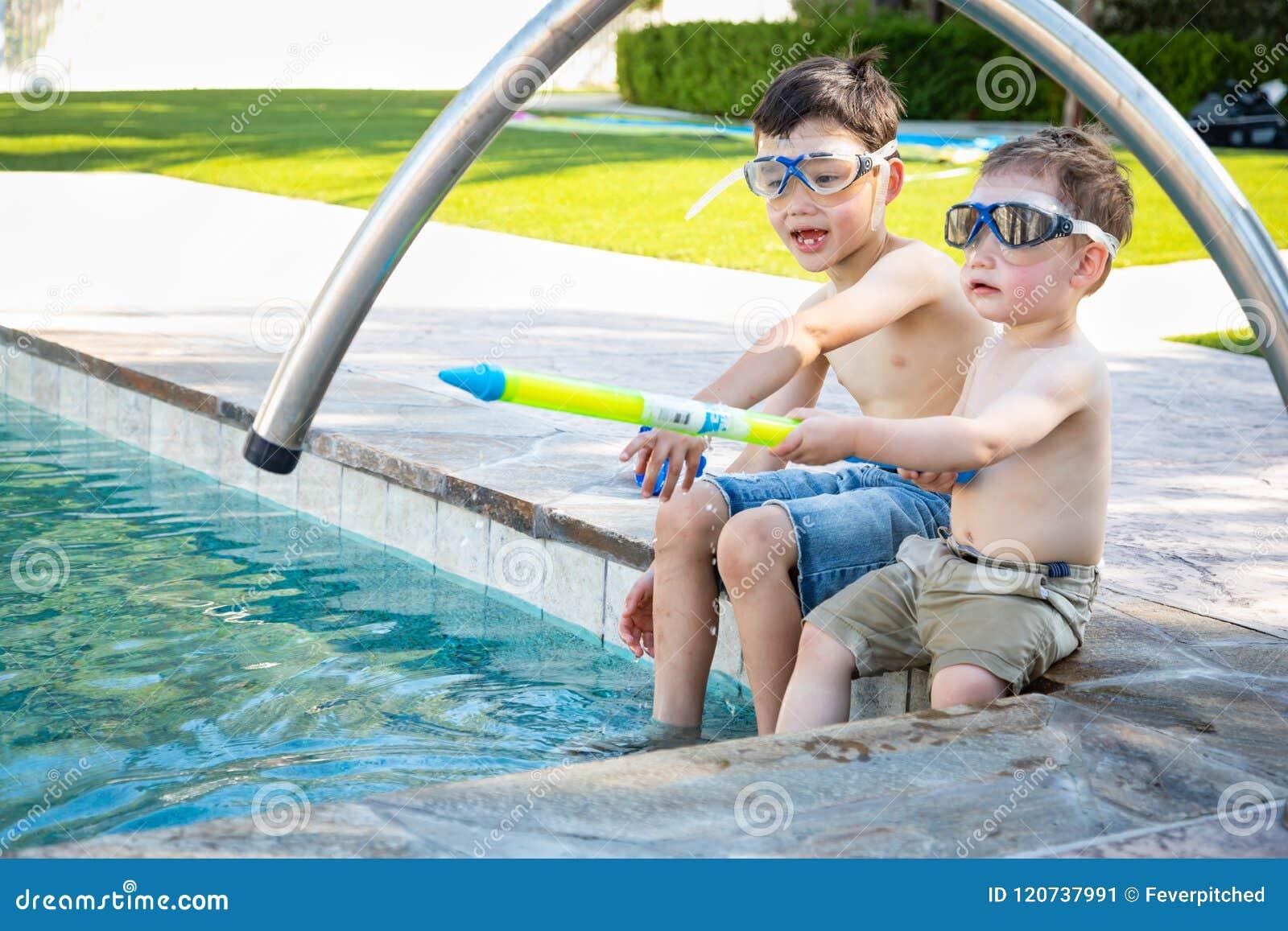 Dois irmãos caucasianos chineses da raça misturada pela associação em óculos de proteção da natação