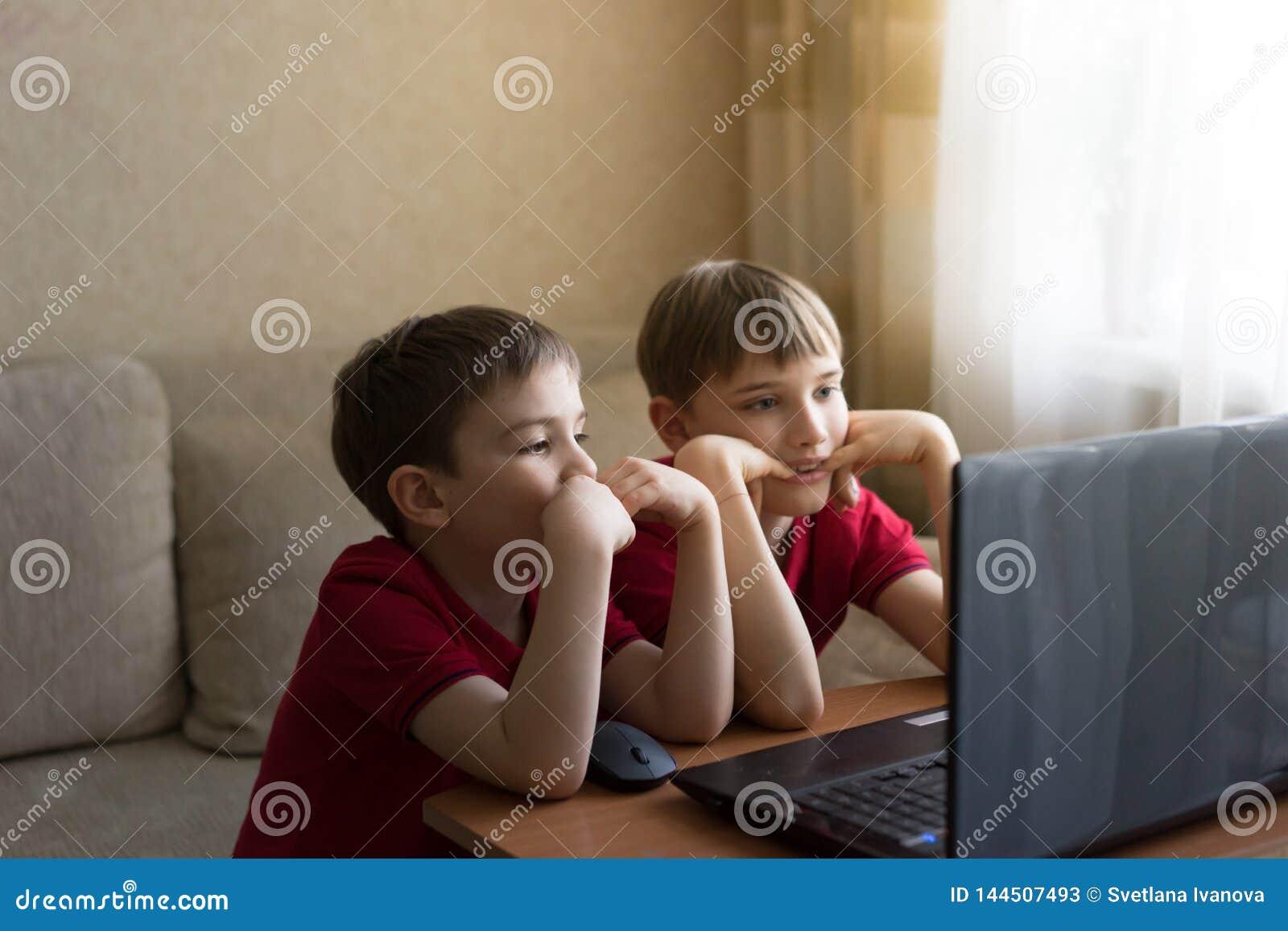 Dois irmãos em t-shirt vermelhos idênticos que olham desenhos animados no computador em casa