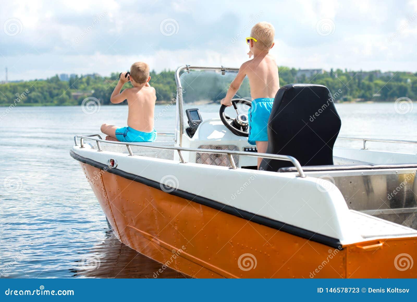 Dois irm?os nadam em um barco de motor no lago
