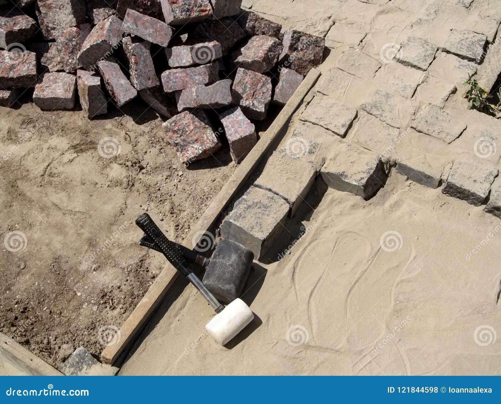 Dois malhos de borracha entre uma pilha de pedras do granito para pavimentar