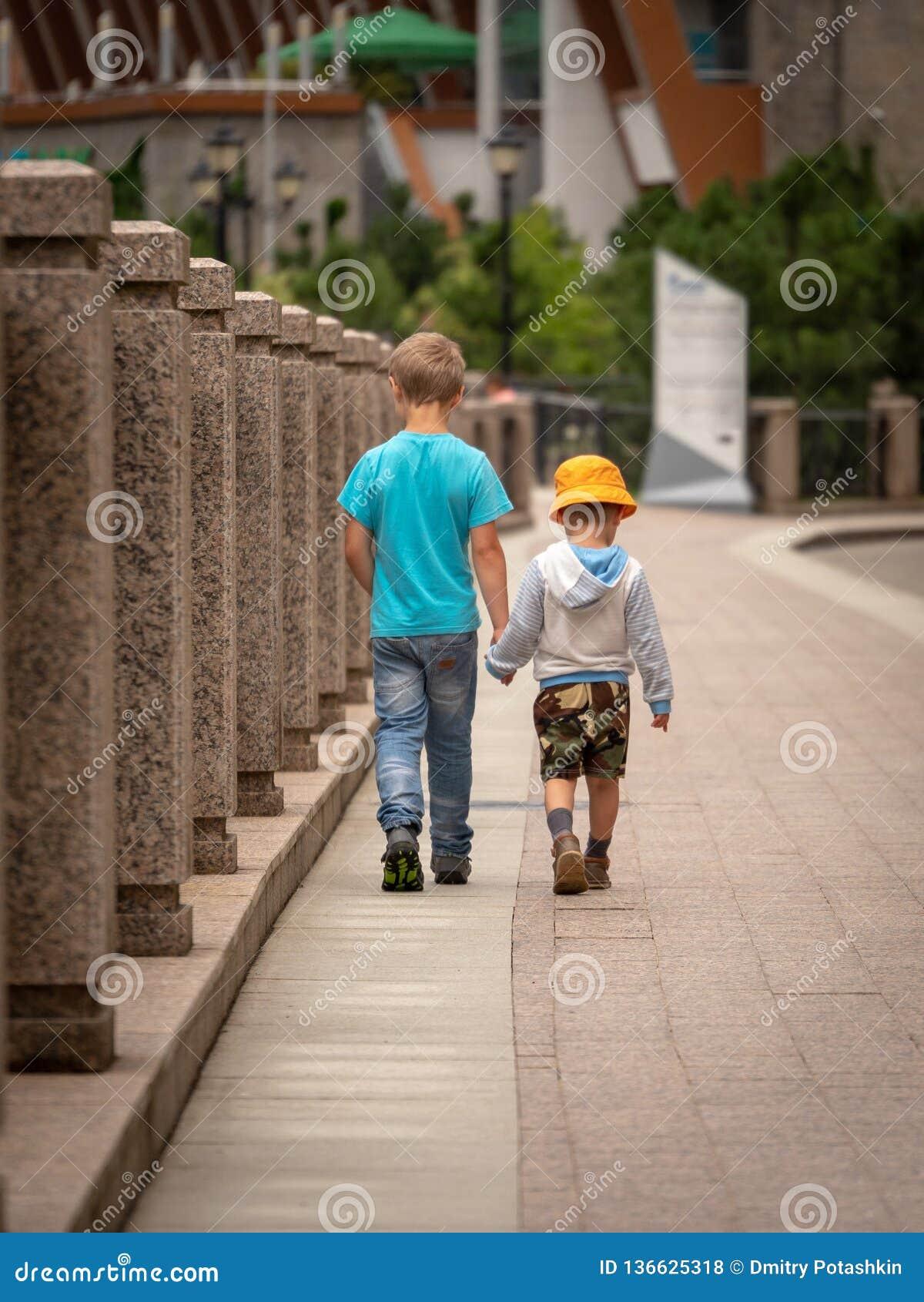 Dois meninos andam ao longo do rio da cidade