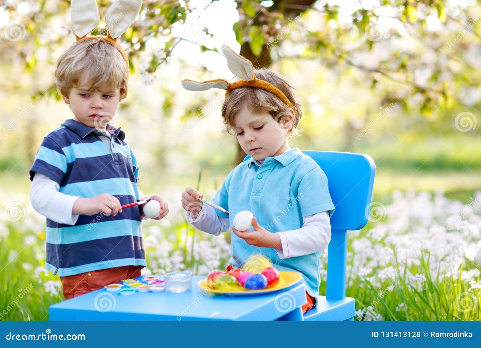 Dois meninos bonitos da criança que vestem as orelhas do coelhinho da Páscoa, ovos coloridos de pintura e tendo o divertimento fo