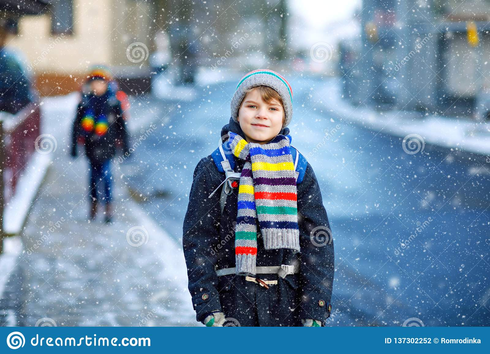 Dois meninos das crianças da classe elementar que andam à escola durante a queda de neve Crianças felizes que têm o divertimento