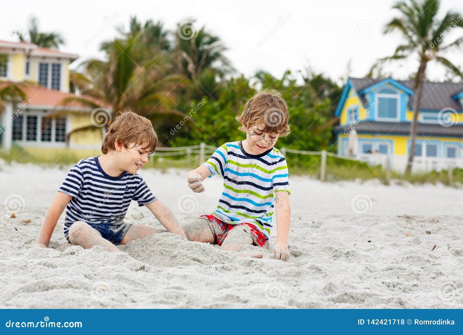 Dois meninos das crianças que têm o divertimento na praia tropical, melhores amigos felizes que jogam, conceito da amizade Irmãos