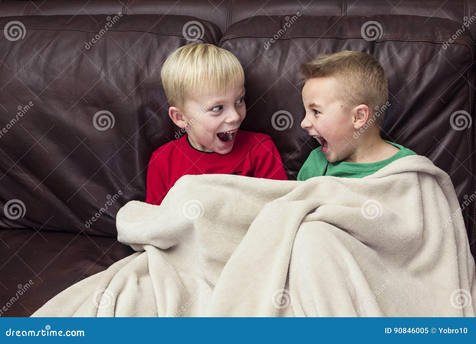 Dois meninos felizes que sentam-se em um sofá que olha a tevê junto