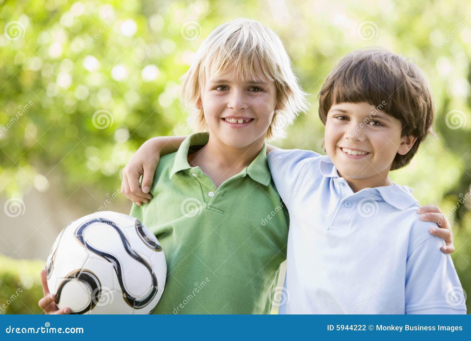 Dois meninos novos ao ar livre com sorriso da esfera de futebol