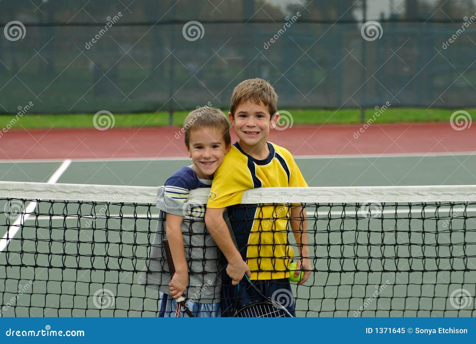 Dois meninos que jogam o tênis