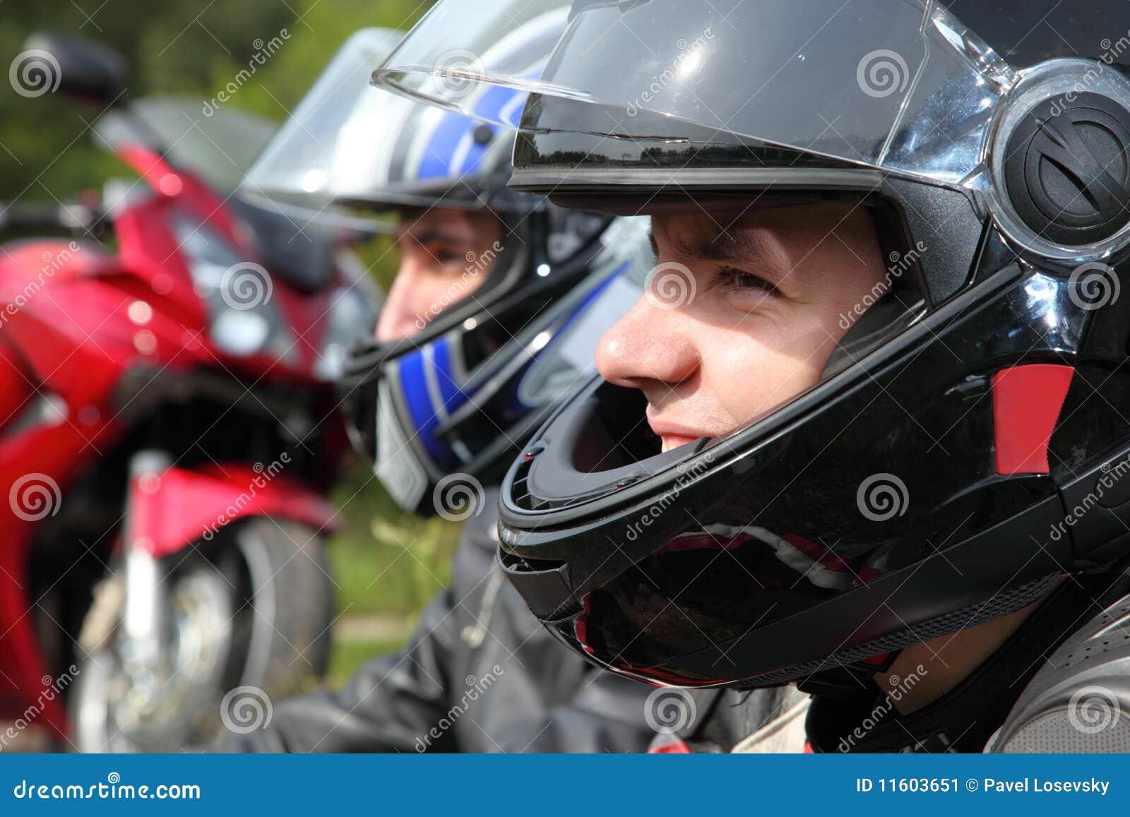 Dois motociclista que sentam-se perto da bicicleta