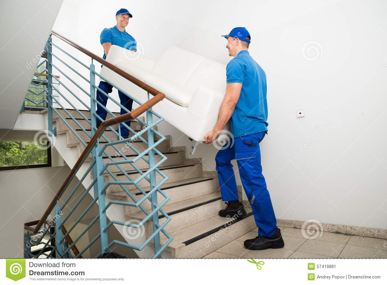 Dois motores masculinos que levam Sofa On Staircase