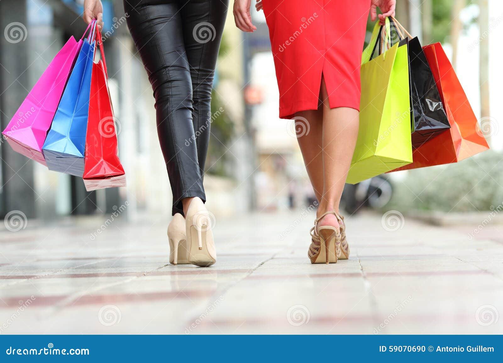 Dois pés das mulheres da forma que andam com sacos de compras