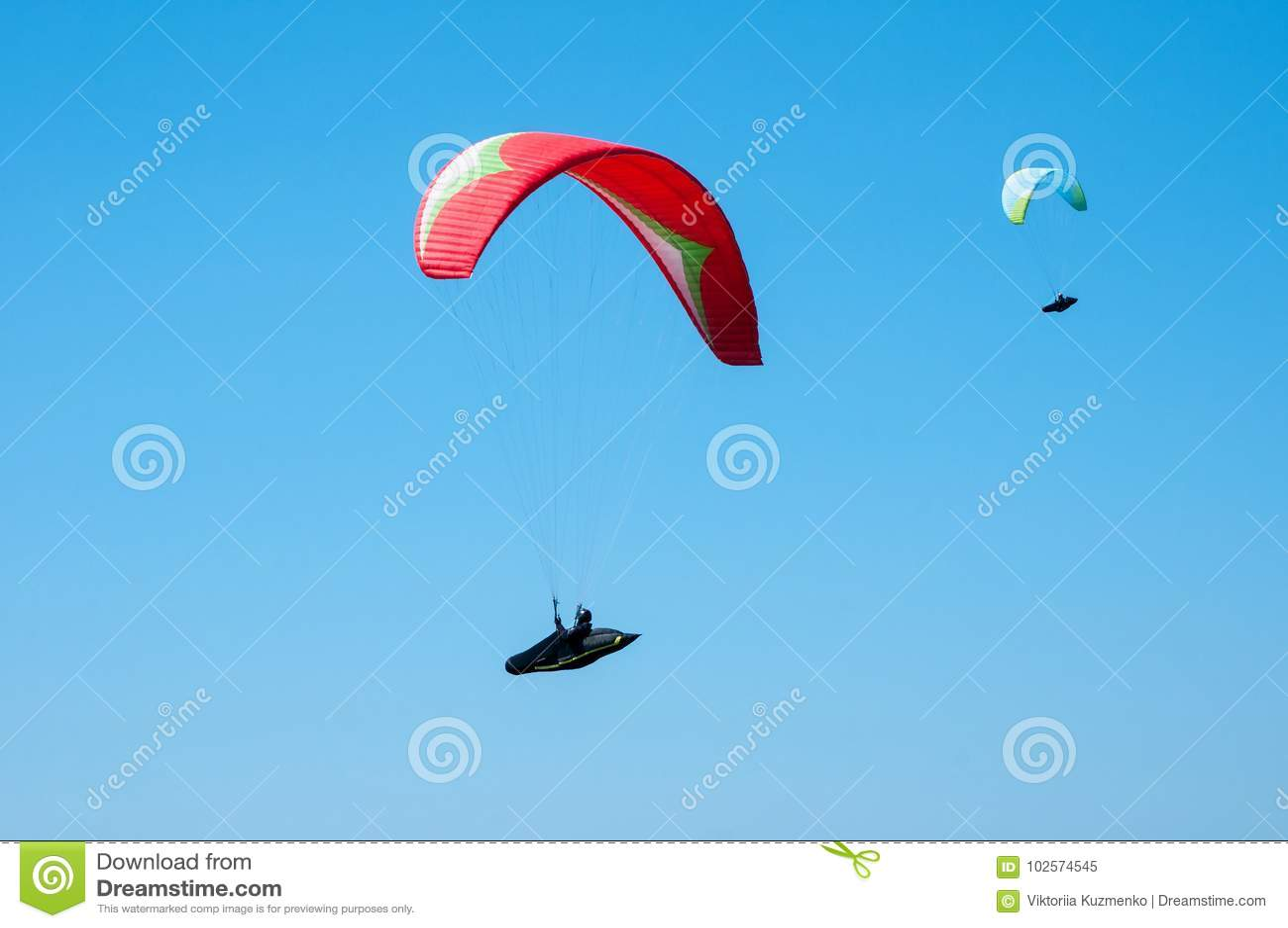 Dois paragliders que voam no céu azul